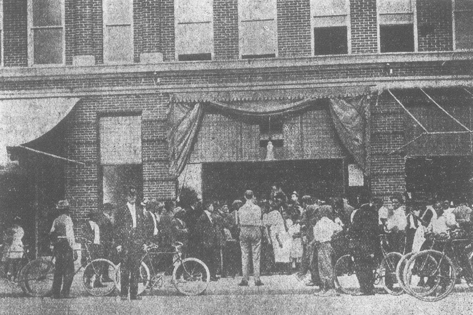 "Customers line up outside the Wreck Store in November 1913. Advertisements offered men's ""furnishings,"" or clothing, at low prices."