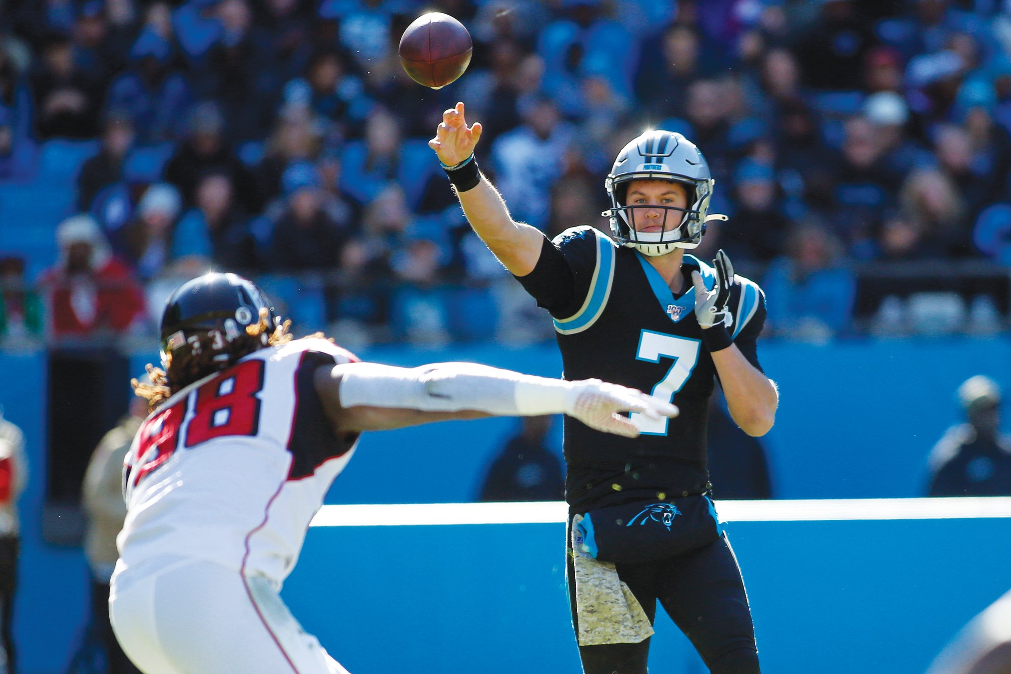 Carolina Panthers quarterback Kyle Allen (7) passes while Atlanta Falcons defensive end Takkarist McKinley (98) defends during the first half of an NFL football game in Charlotte, N.C., Sunday, Nov. 17, 2019.