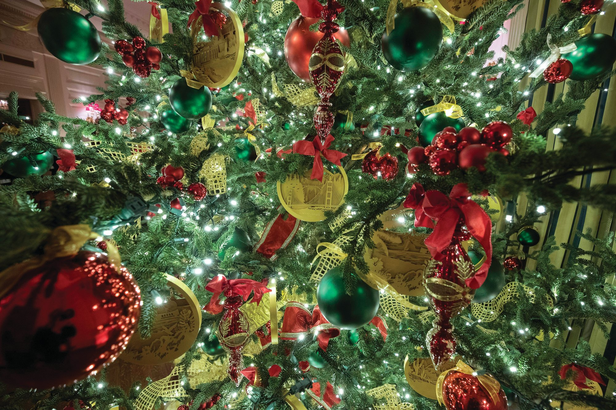 A tree in the State Dining Room is decorated with traditional red, green and gold.