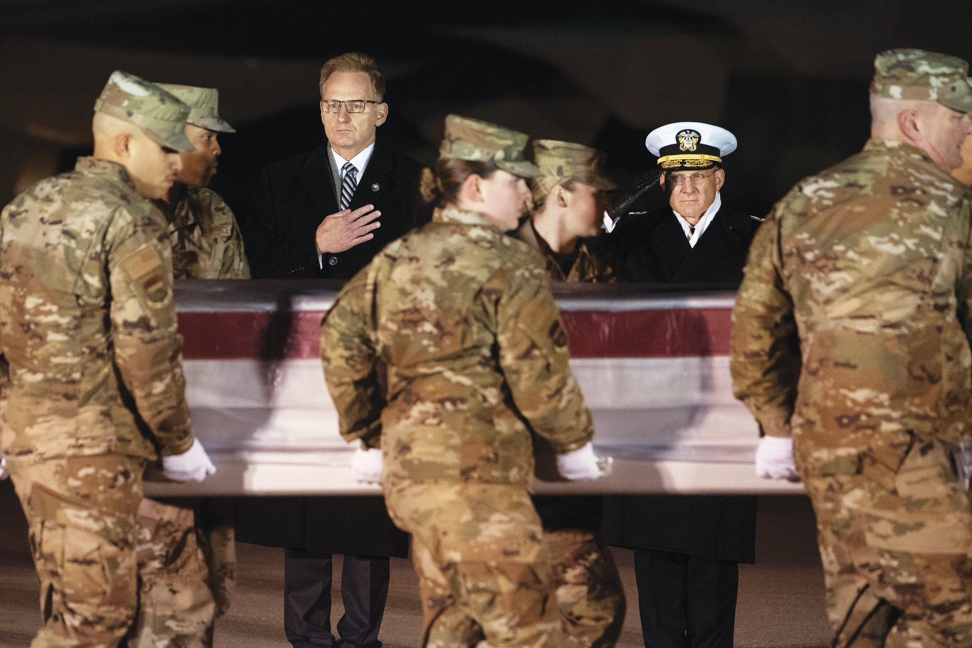 Acting Navy Secretary Thomas Modly, center, and Navy Adm. Michael Gilday, Chief of Naval Operations, look on as an Air Force carry team moves a transfer case containing the remains of Navy Seaman Mohammed Sameh Haitham, of St. Petersburg, Fla., Sunday, Dec. 8, 2019, at Dover Air Force Base, Del. A Saudi gunman killed three people including Haitham in a shooting at Naval Air Station Pensacola in Florida.