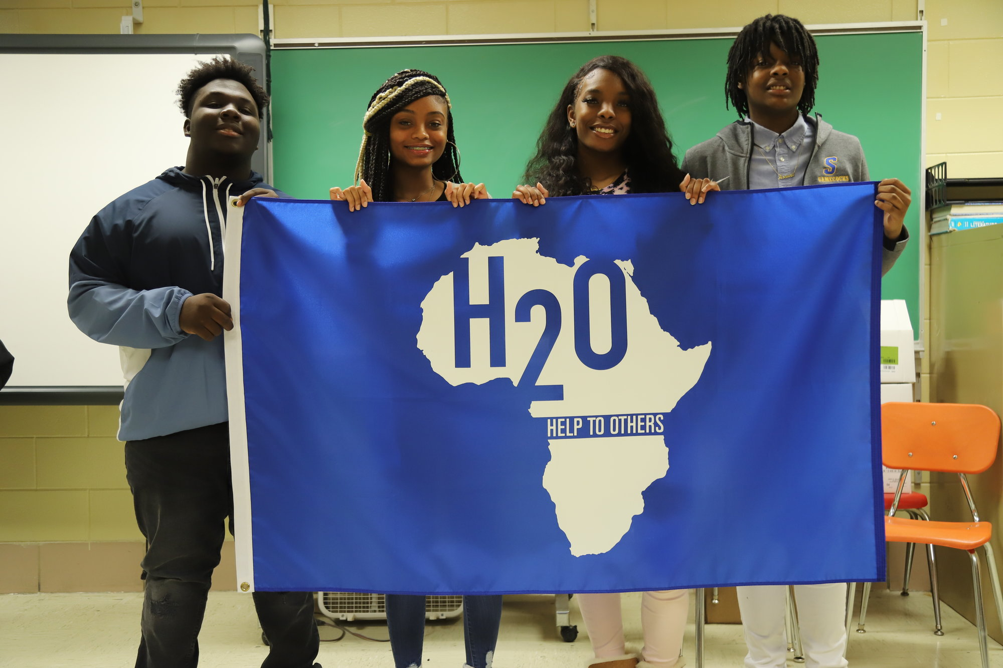 BRUCE MILLS / THE SUMTER ITEMFrom left, Sumter High School junior AVID students Robert Lancaster, Aniya Newkirk, Danesia Carter and Inga Colclough hold an H2O for Life banner flag on Friday at the school.