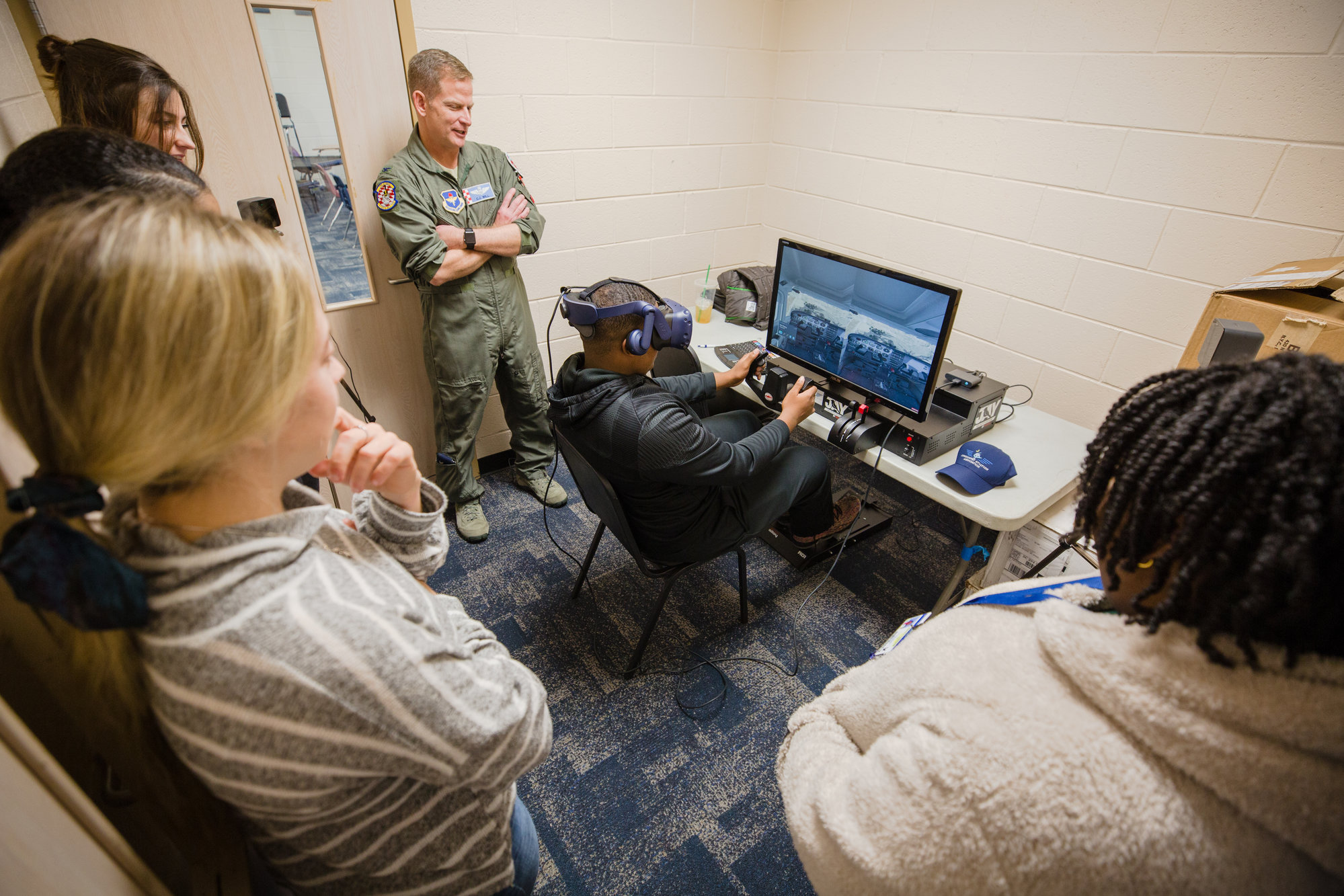 A Scott's Branch High School student uses a flight simulator as Col. Will and other students look on.