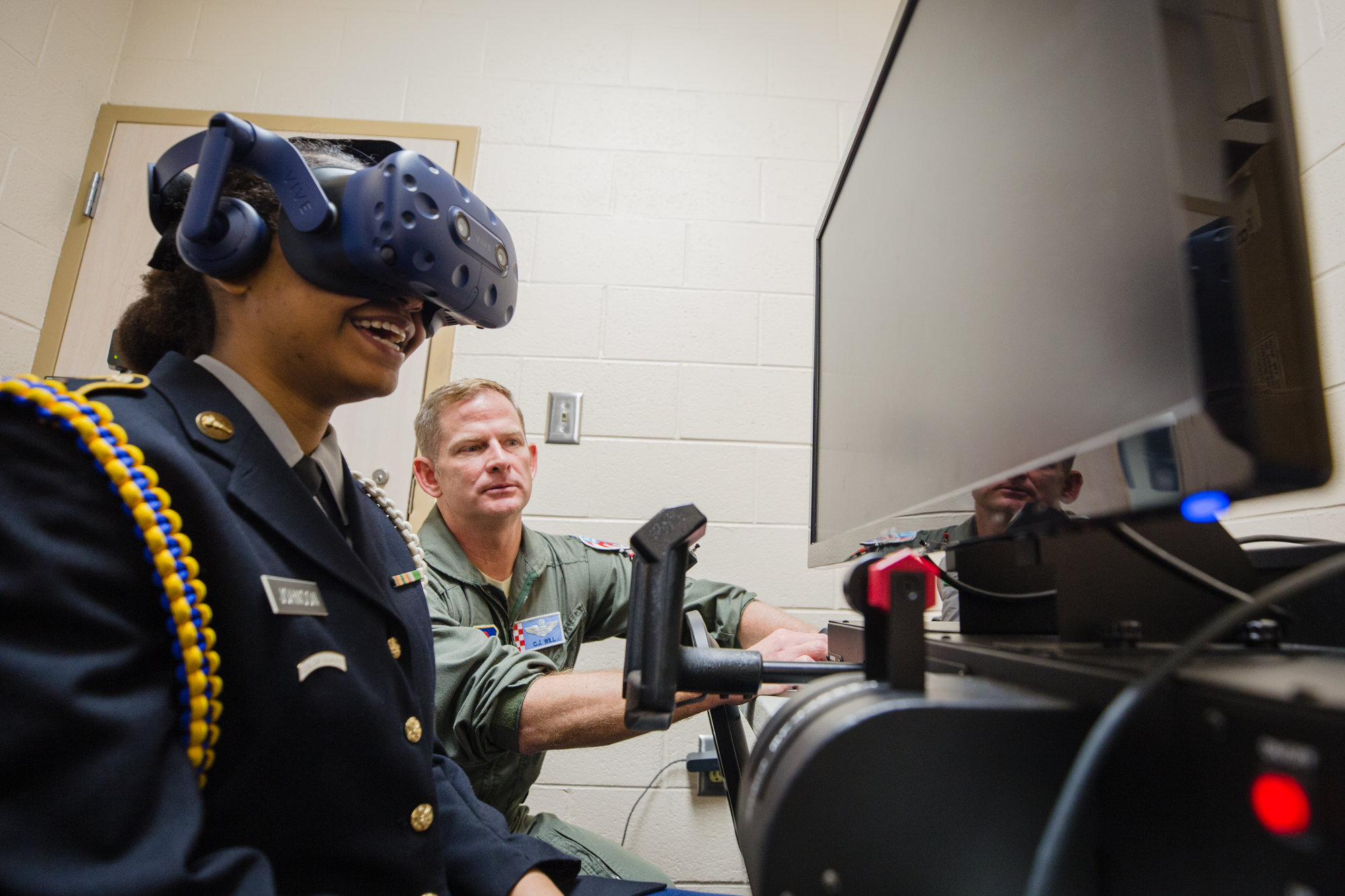 Ja'Nya Johnson uses a flight simulator as Col. Christopher J. Will, commander, 765th Detachment, Air Force Reserve Officer Training Corps, looks on. Will spoke during a program at Scott's Branch High School on Wednesday to encourage students to look into working in the aviation field after they graduate.