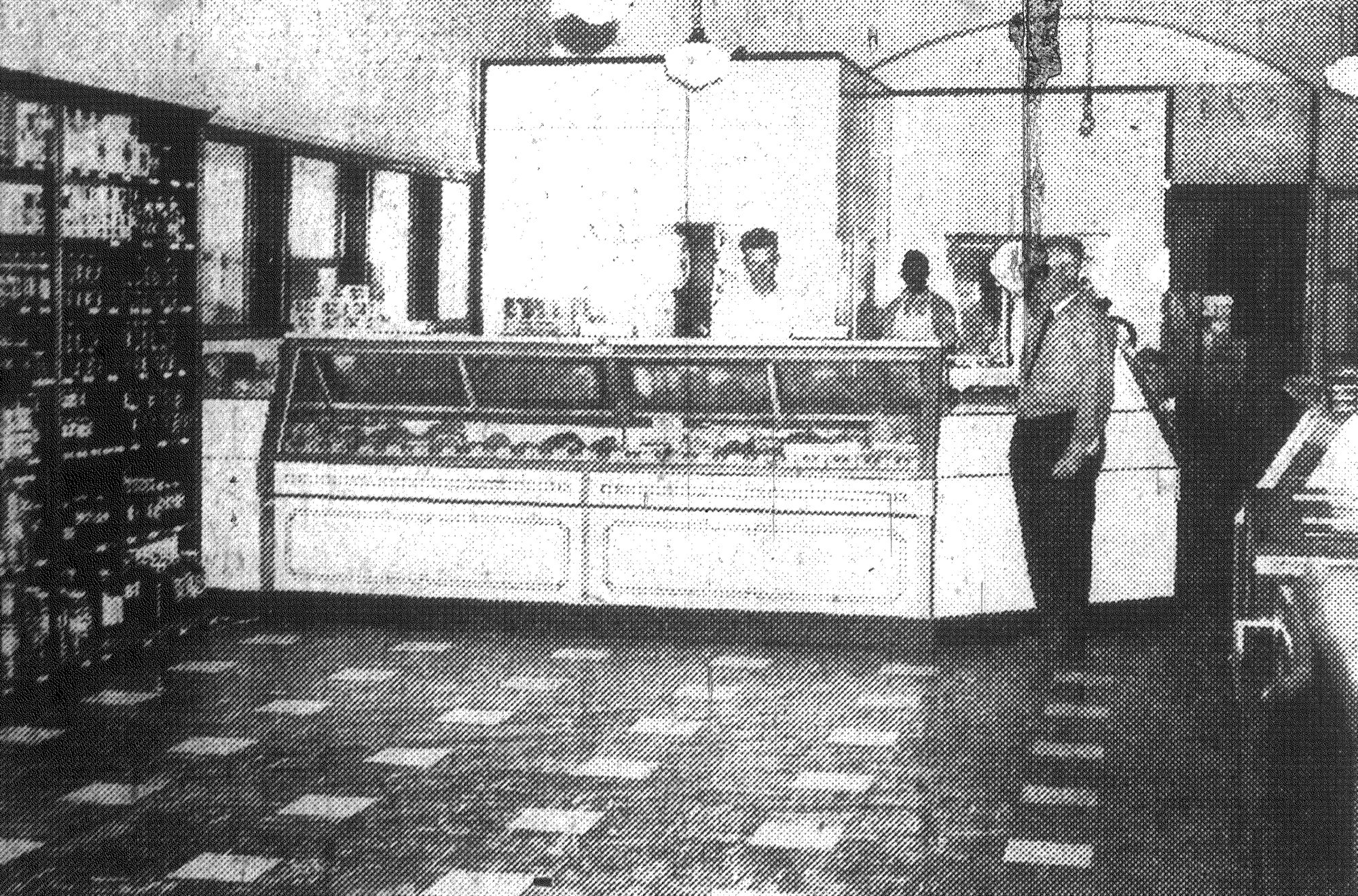 "The meat market at H. J. Commins' remodeled store featured quality meats and built up an unusually large business since it was established. Standing in front of the case is H. J. Commins, and behind the counter is Norwood ""Buck"" Epperson, meat market manager."