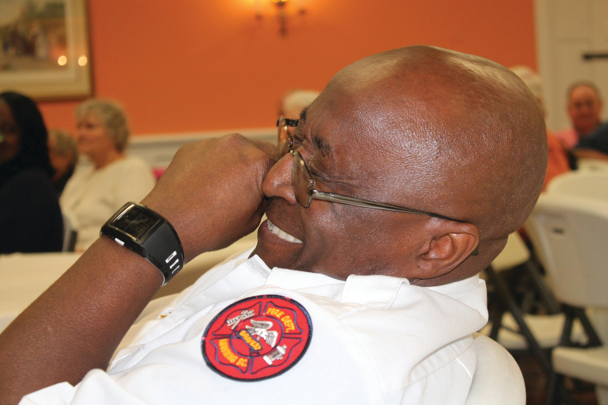 "PHOTOS BY SHARRON HALEY / THE SUMTER ITEM  Capt. James ""Hound Dog"" Pringle chuckles as Manning Fire Chief Mitch McElveen describes the captain's various ""beyond the call of duty"" efforts prior to presenting Pringle with the department's prestigious Beyond the Call of Duty award."
