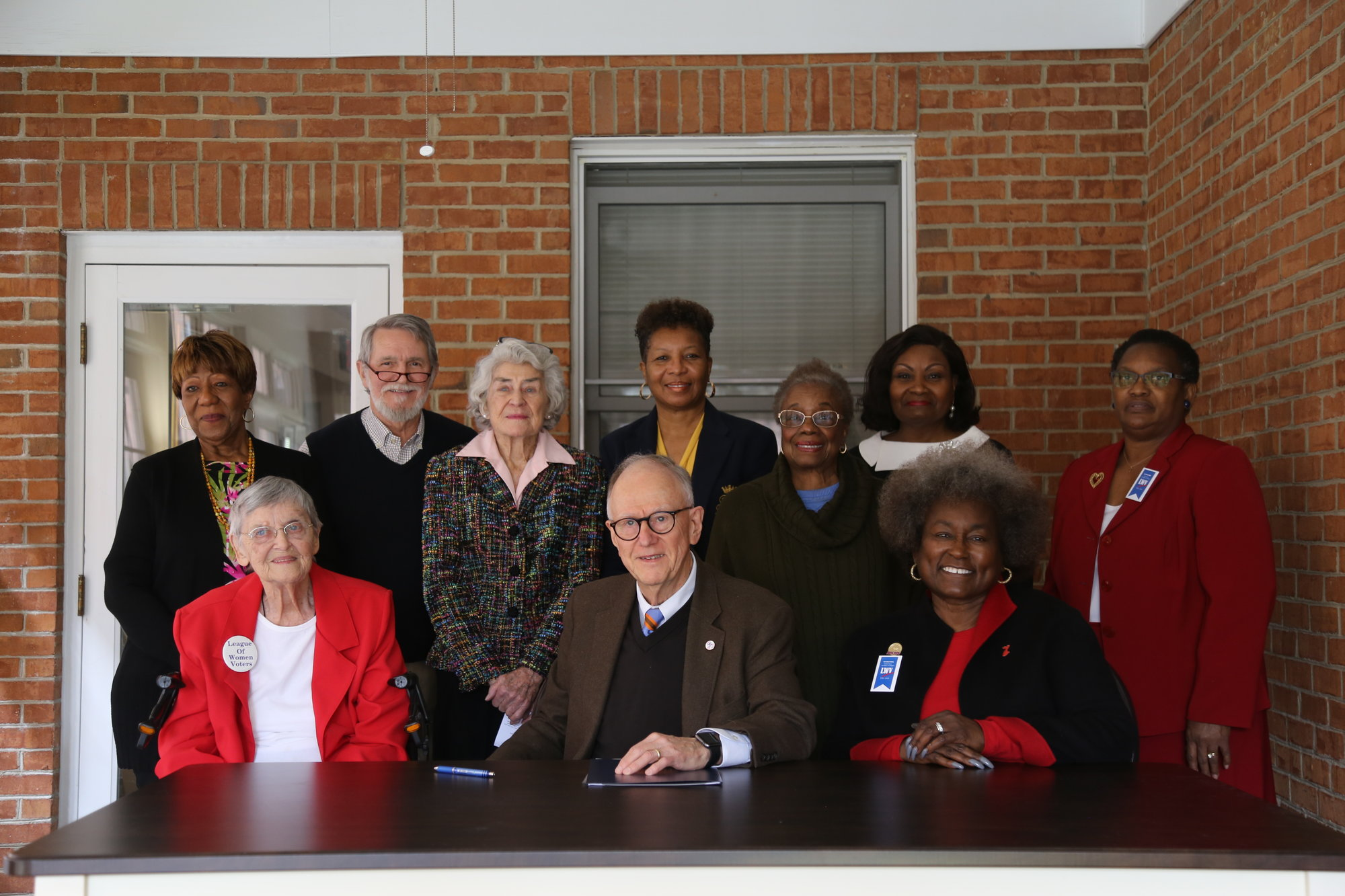 "Sumter Mayor Joe McElveen signs a proclamation stating that February 2020 will be known as ""League of Women Voters Centennial Month"" with members of the League of Women Voters of Sumter County."