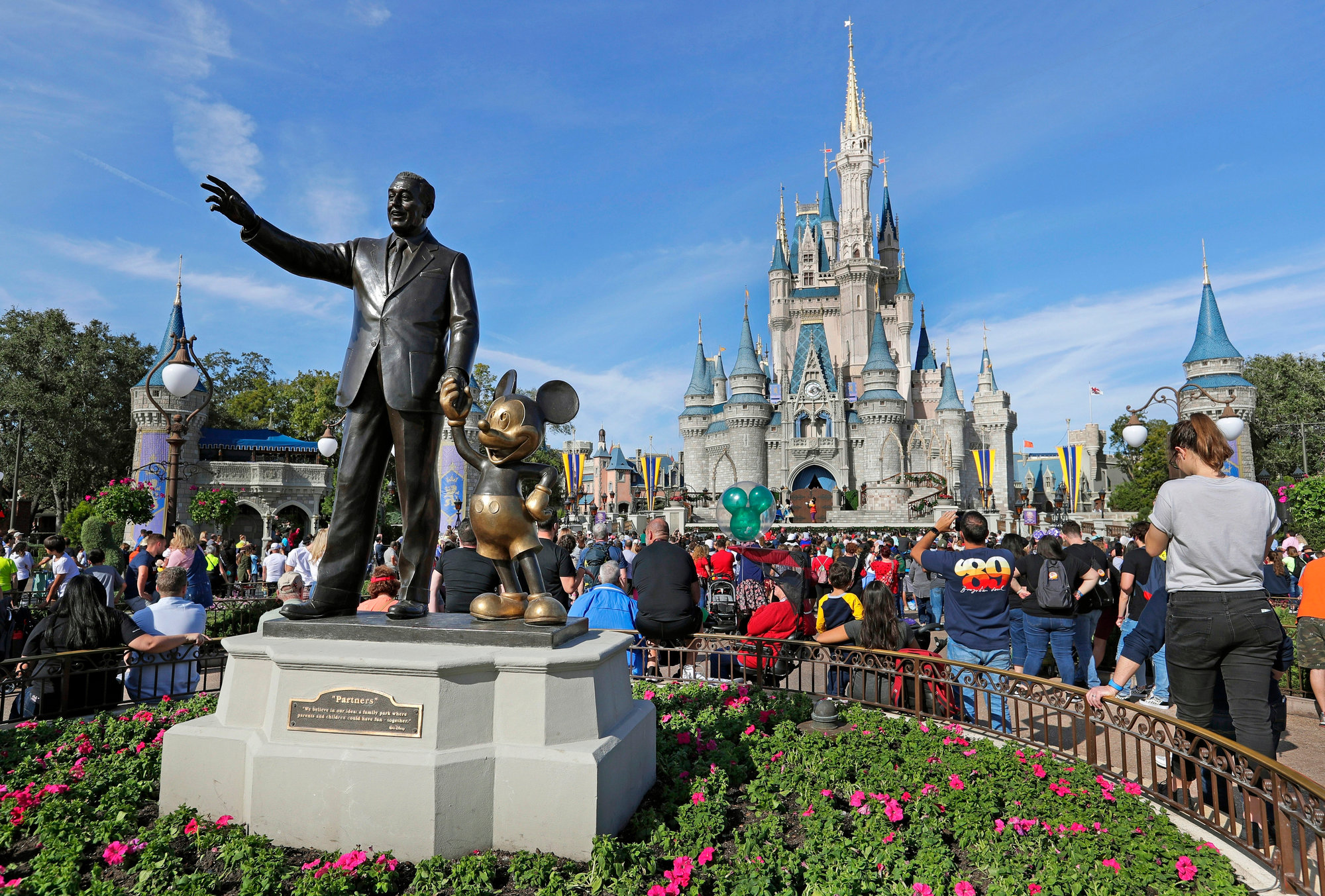 In this Jan. 9, 2019 photo, guests watch a show near a statue of Walt Disney and Micky Mouse in front of the Cinderella Castle at the Magic Kingdom at Walt Disney World in Lake Buena Vista, Florida.
