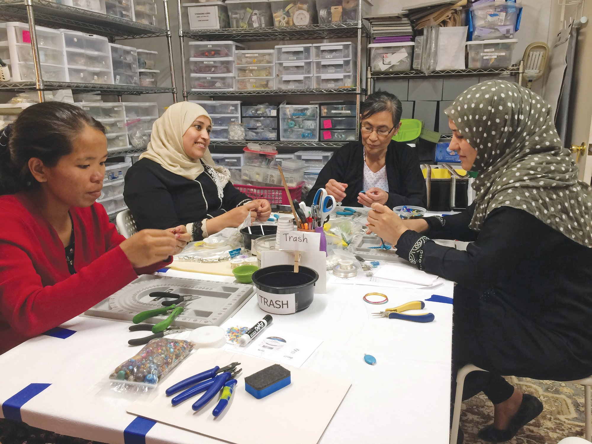 Photos by Sharon L. McCreary via APFrom left, A Little Something participants Khei Hung from Burma, Sabah Almobarak from Syria, Eh Gay Ju from Burma and Mounira Kuru from Syria work through frustration and creative challenges in their first lesson making wire-wrapped necklace pendants. A Little Something not only helps refugees find community, but it also sells the crafts and gives artisans 75% of the earnings.