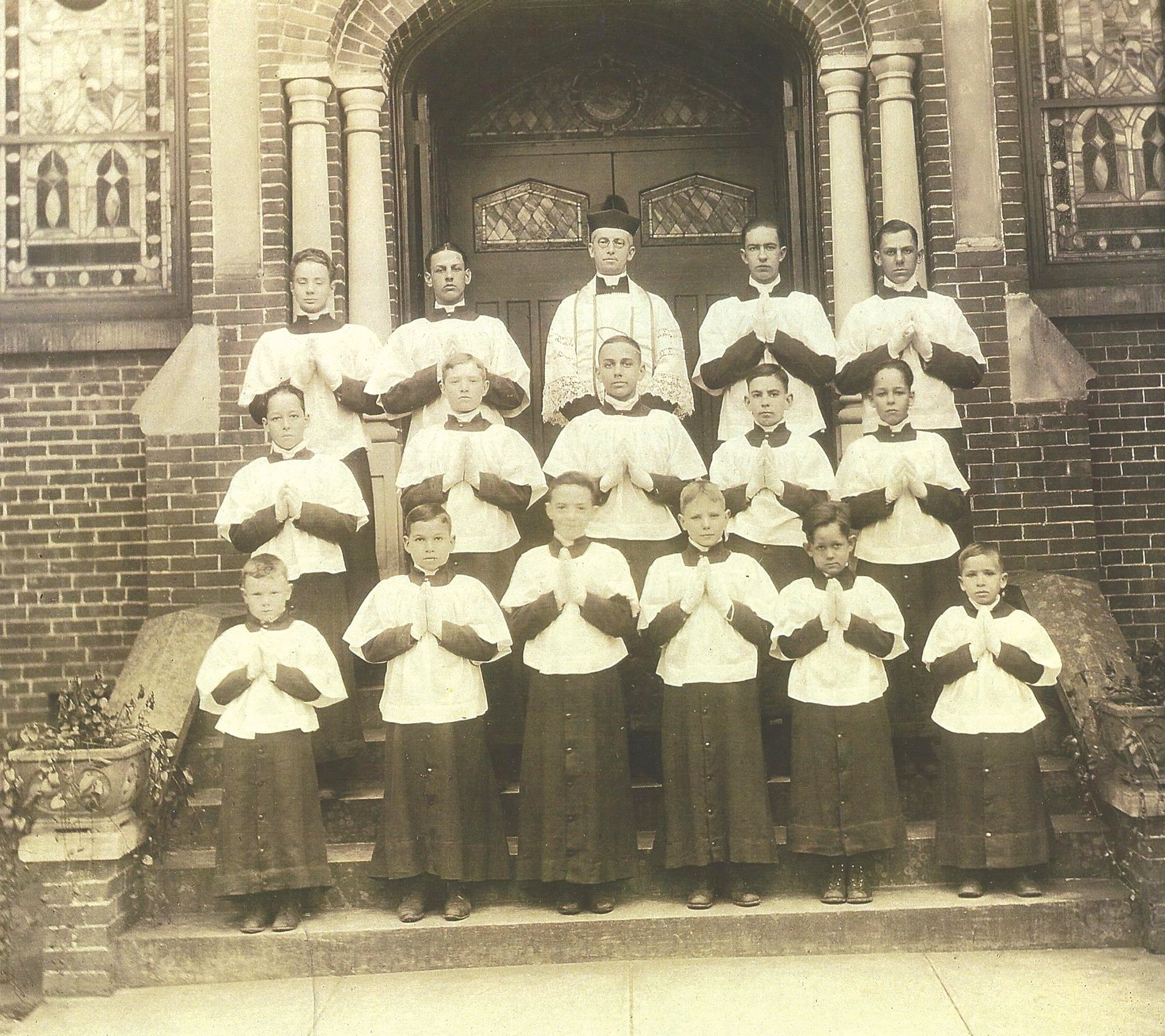 St. Anne Catholic Church's pastor and altar boys are seen in 1920. First row from left are Werber Bryan, Louis Persighn, Bernard Epperson, Clemont Bryan, Ashley Mood, Joseph Persighn. Second row from left are Mood's twin (Norwood or Preston), Frances Epperson, John Brennan, Jack McKiever, Mood's other twin. Third row from left are William Bryan, Charles Crombe, Father Joseph Mahoney, George McKiever and Robert Bultman.