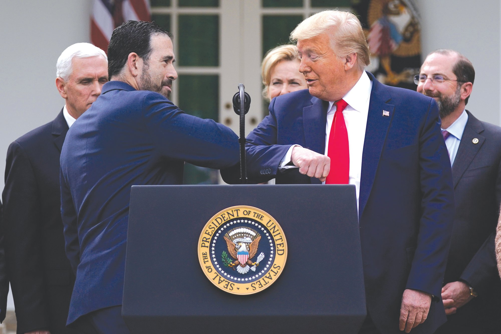 LHC Group's Bruce Greenstein elbow bumps with President Donald Trump during a news conference about the coronavirus in the Rose Garden at the White House on March 13 in Washington.