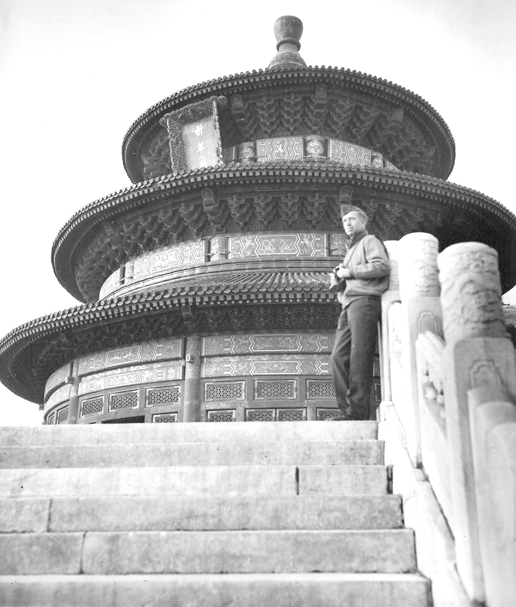 Combat photographer Heyward Crowson stands on the steps of a Chinese temple in Tientsin, China.