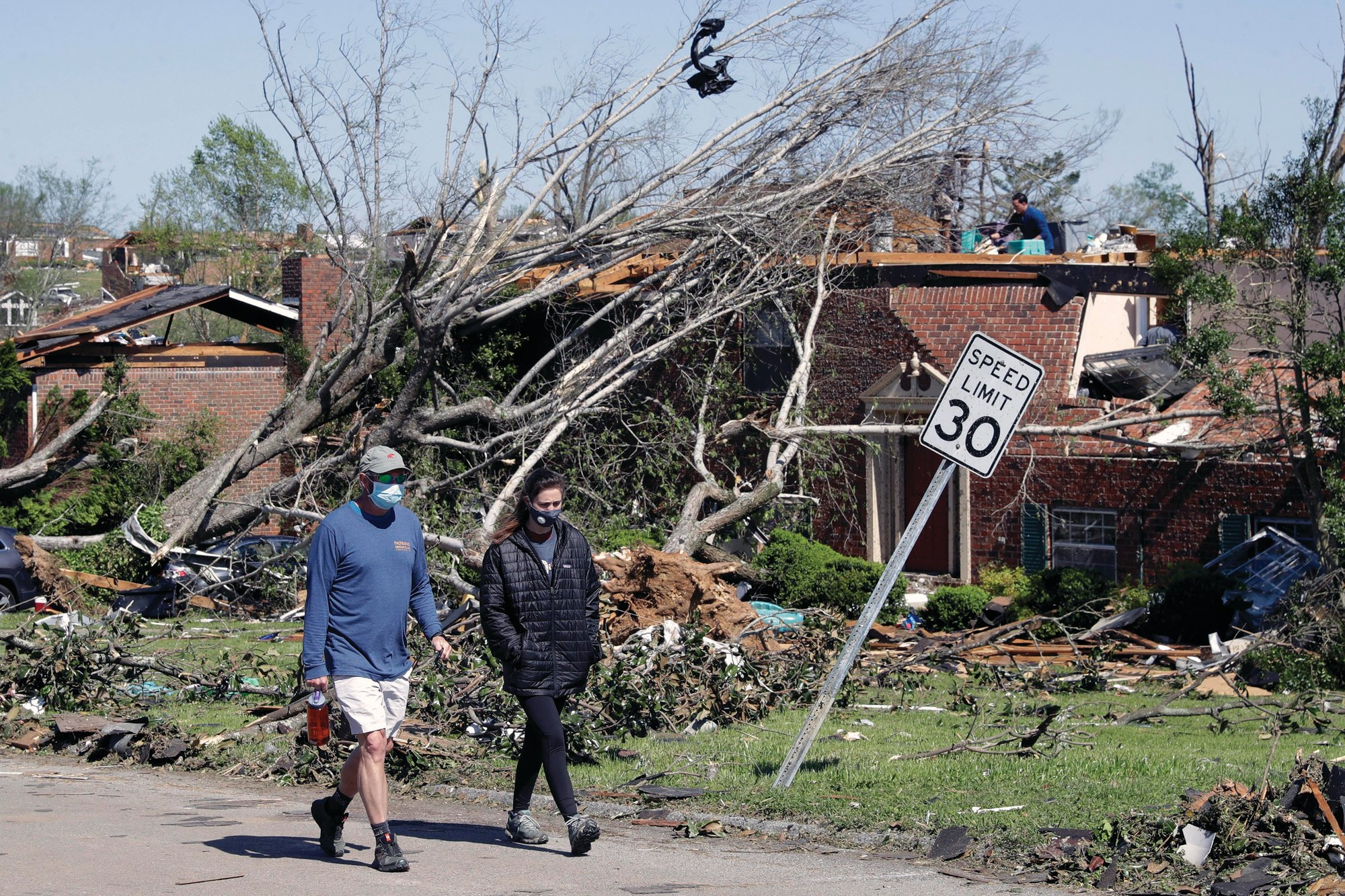 People walk up a street of damaged homes Tuesday, April 14, 2020, in Chattanooga, Tenn. Tornadoes went through the area Sunday, April 12.