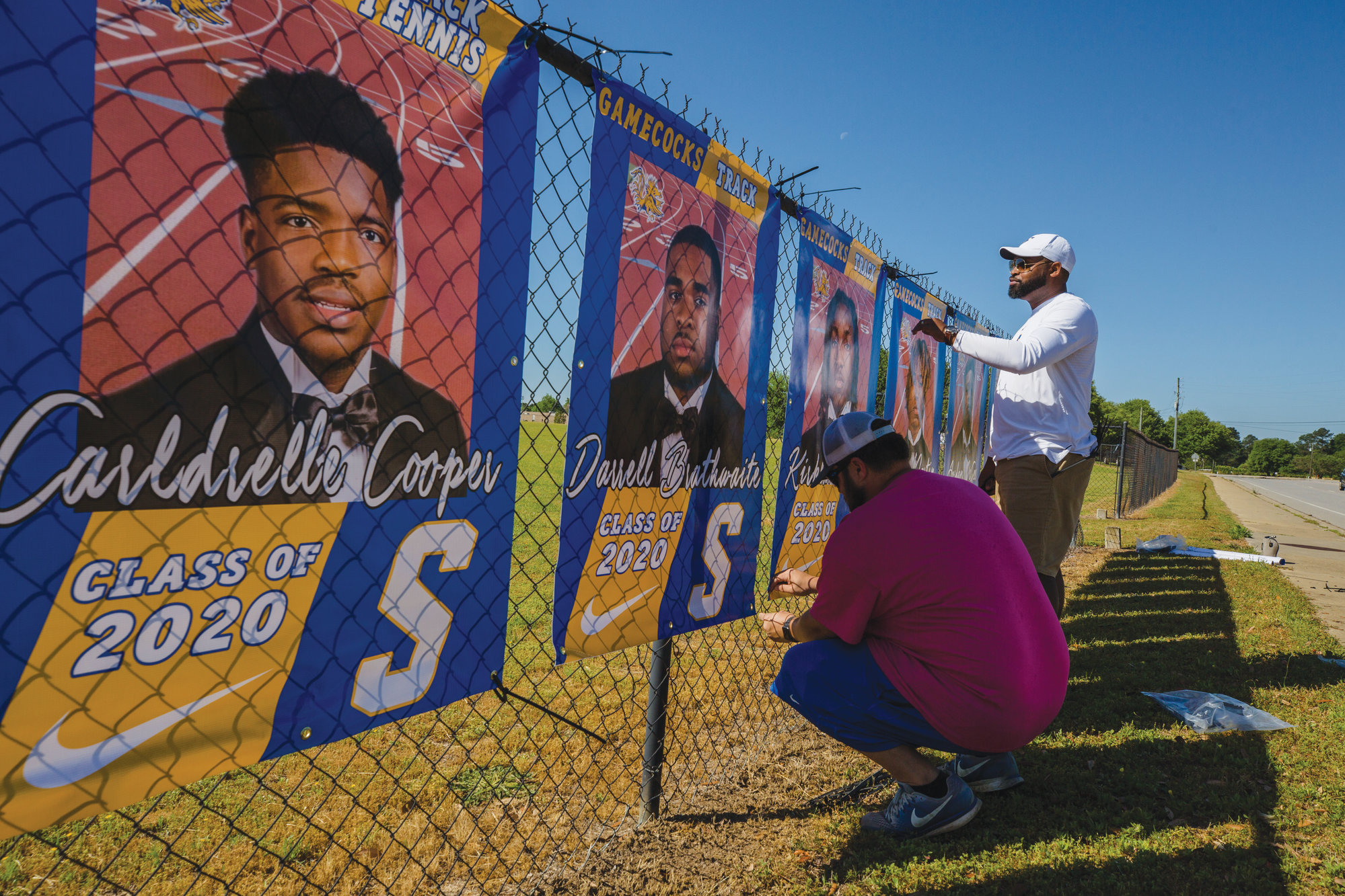 Sumter athletic director Curtis Johnson, left, and principal Nicholas Pearson hang some of the banners for the 48 senior spring sports student-athletes.