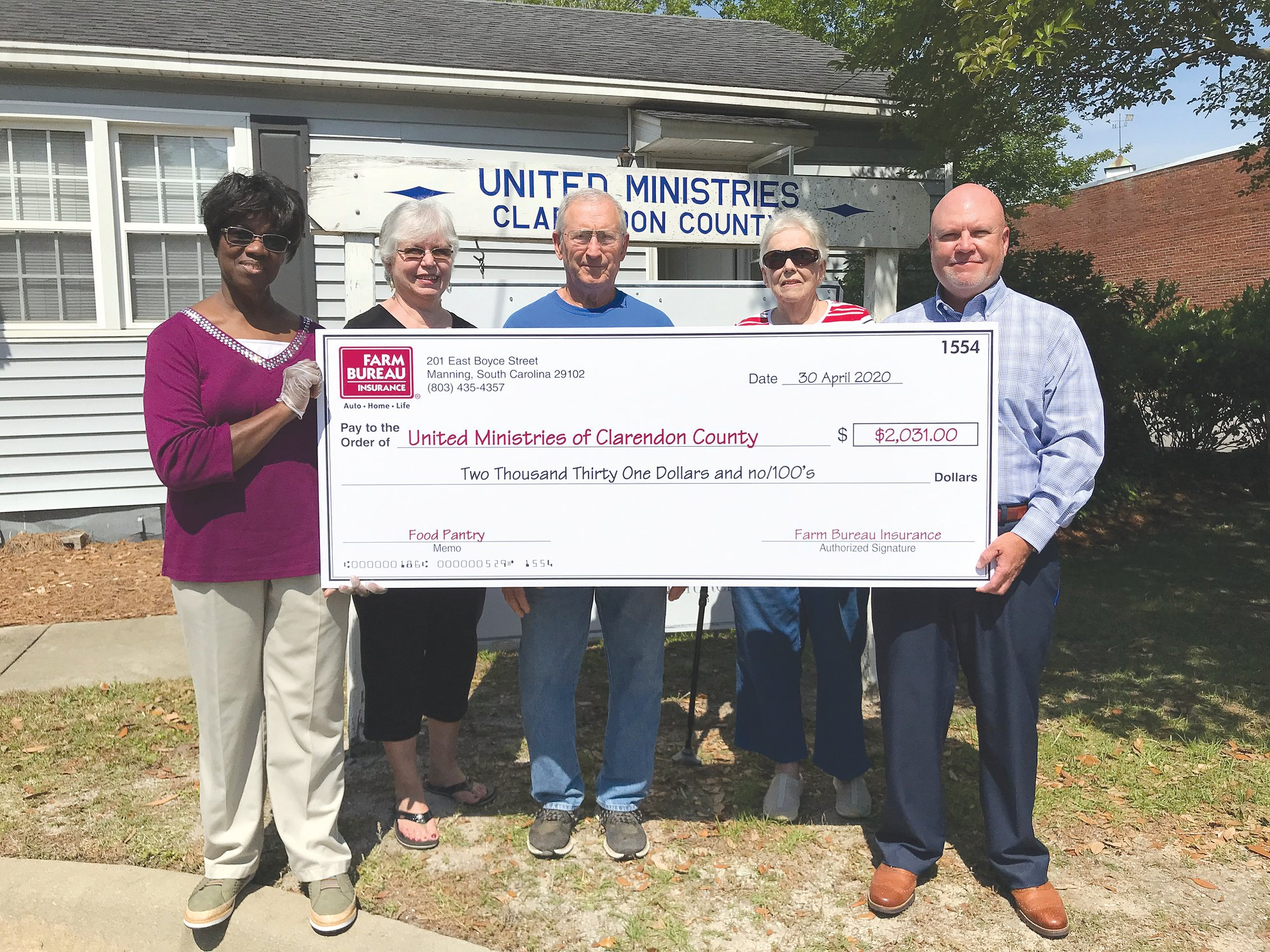 From left, Lou S. Nelson, Jane Hamrick and Travis Brown, volunteers for United Ministries of Clarendon County; Mary Queen, manager of Manning First Baptist Church's Friendship House; and Wayne McKenzie, Farm Bureau agency manager, are seen holding the check that agents from Manning Farm Bureau made possible.