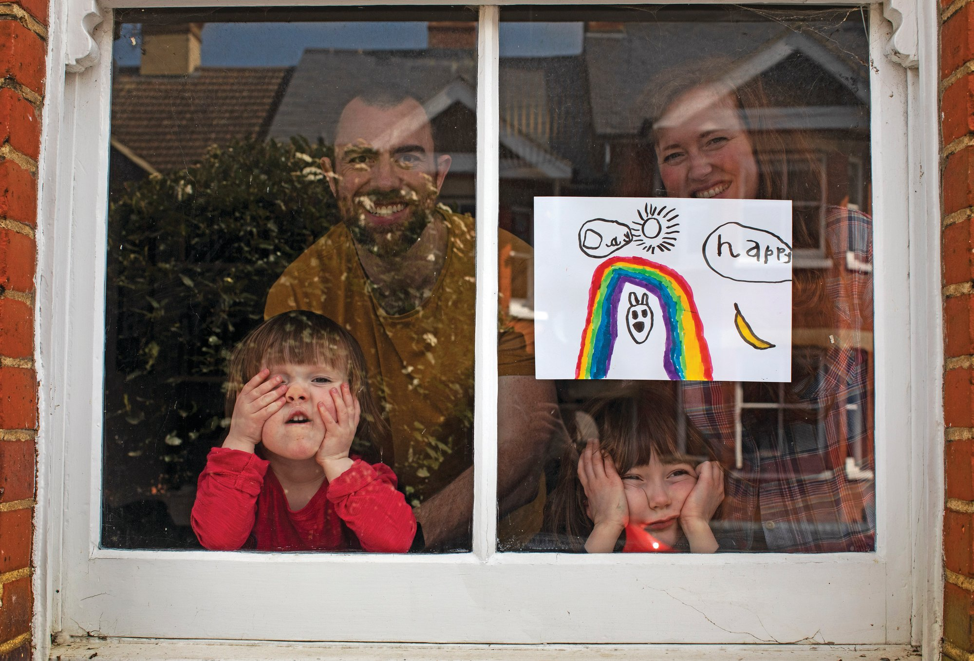 Amelie and her sister, Camille, watch from their front window as the lockdown enters its third week along with their parents, Victoria and Damian Kerr, in Berkhamsted on April 4. Victoria and Damian are both working full time from home but are enjoying the chance the lockdown has given them to spend more time together as a family despite its challenges.