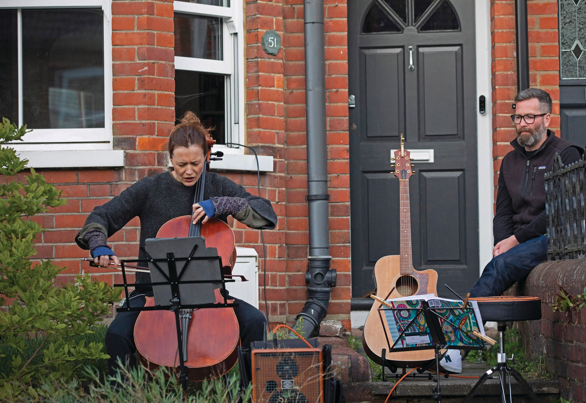 Clare O'Connell, a concert cellist, and her husband, Dom Shovelton, a composer, offer an impromptu concert from their front door as neighbors flock to listen while observing social distancing on the street in Berkhamsted, London, on May 2. As the coronavirus lockdown tightened and people shut their doors, neighbors began introducing themselves to one another online, building a community on the street.
