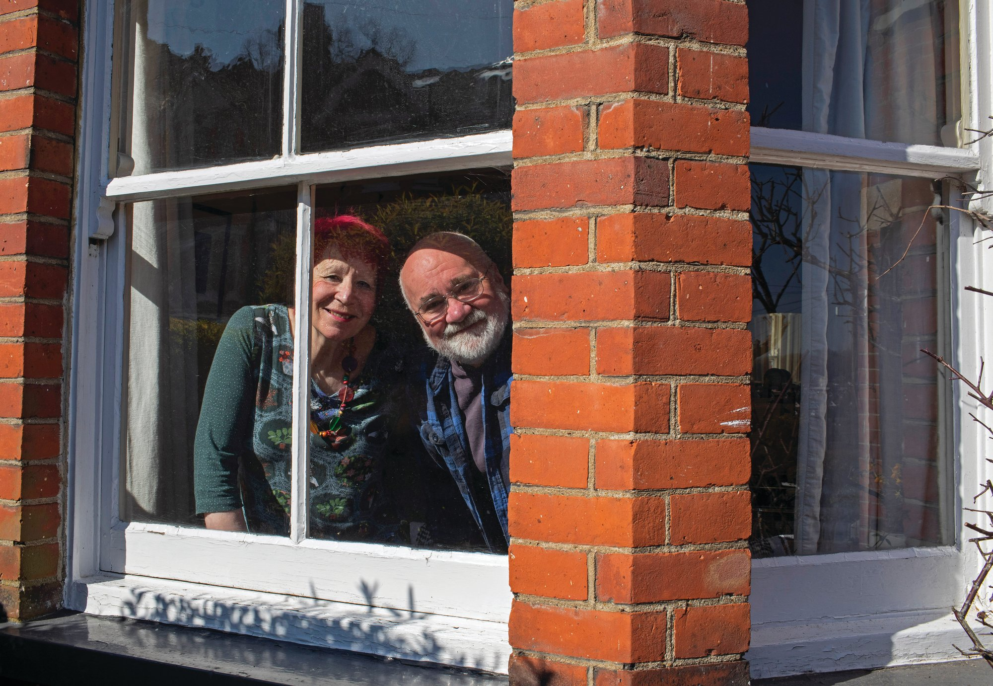 Bob and Sue Parsons look out from their window in Berkhamsted on March 26. The couple, who has lived there for 40 years, has seen changes on the street, but this is by far the strangest time they have lived through.