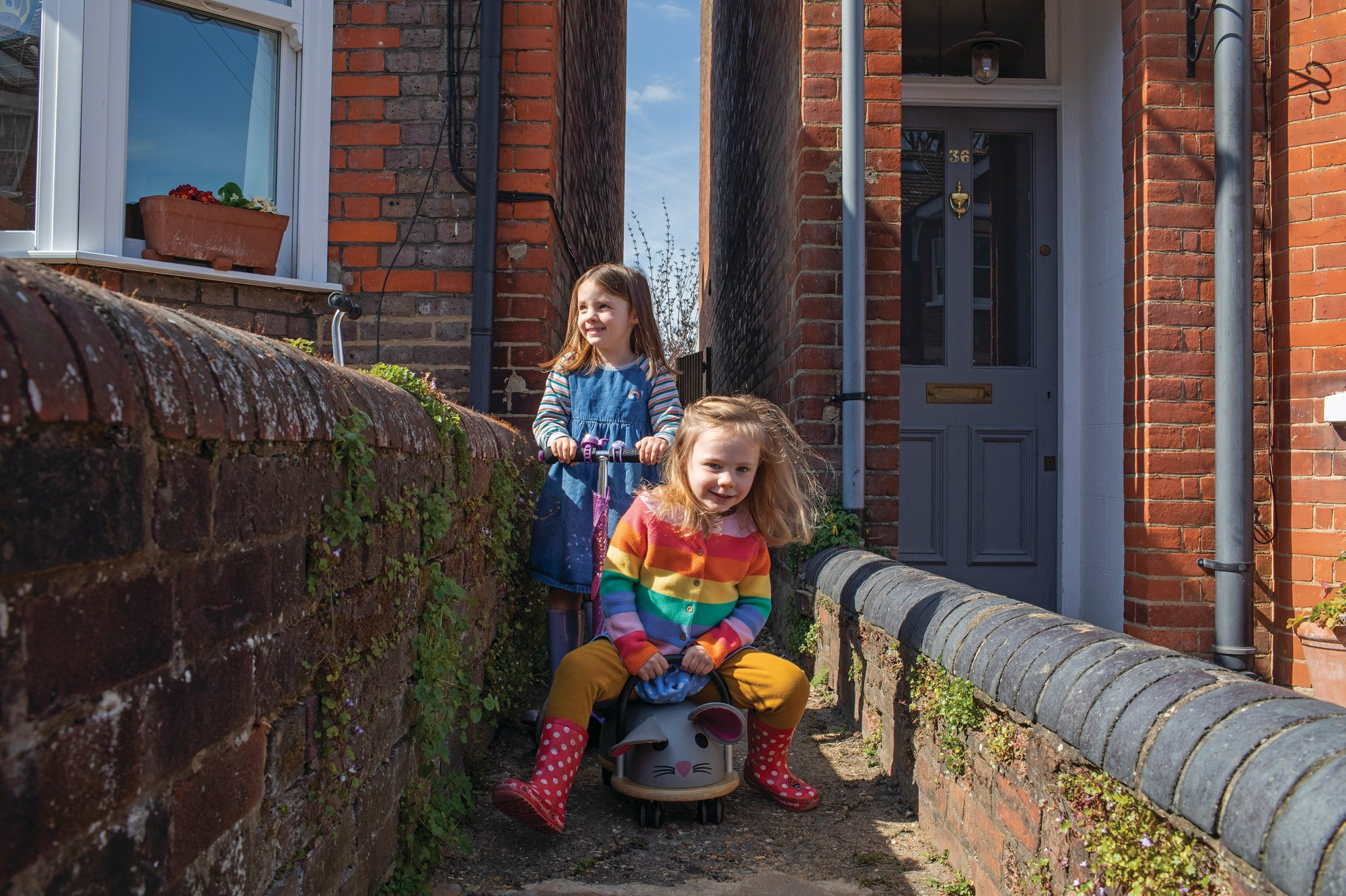 Astrid, 5, and Martha, 3, enjoy a scoot along their home's alley and a little freedom in Berkhamsted on April 7. Matt Leuw, their dad, recently recovered from the coronavirus and self isolated at home. Rachel, their mom, works as a program manager at the NHS Royal Free Hospital.