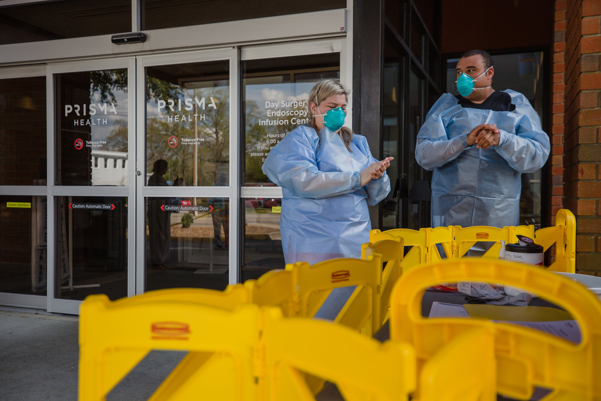 Chloe Peters, an RN at Prisma Health Tuomey Hospital, and Kyle Sanders, a BLS specialist with Prisma Health, wash up after conducting and collecting a drive-through COVID-19 test in Sumter in mid-March.