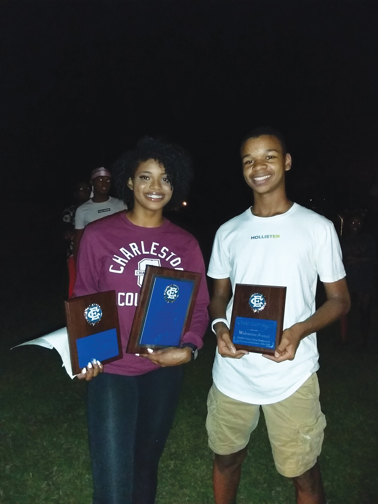 East Clarendon's Alicia Wilson, left, and Chris Barringer receive their plaques from the school's sports banquet, which coaches took on the road to each of the students' houses on Thursday night and throughout the day on Friday.