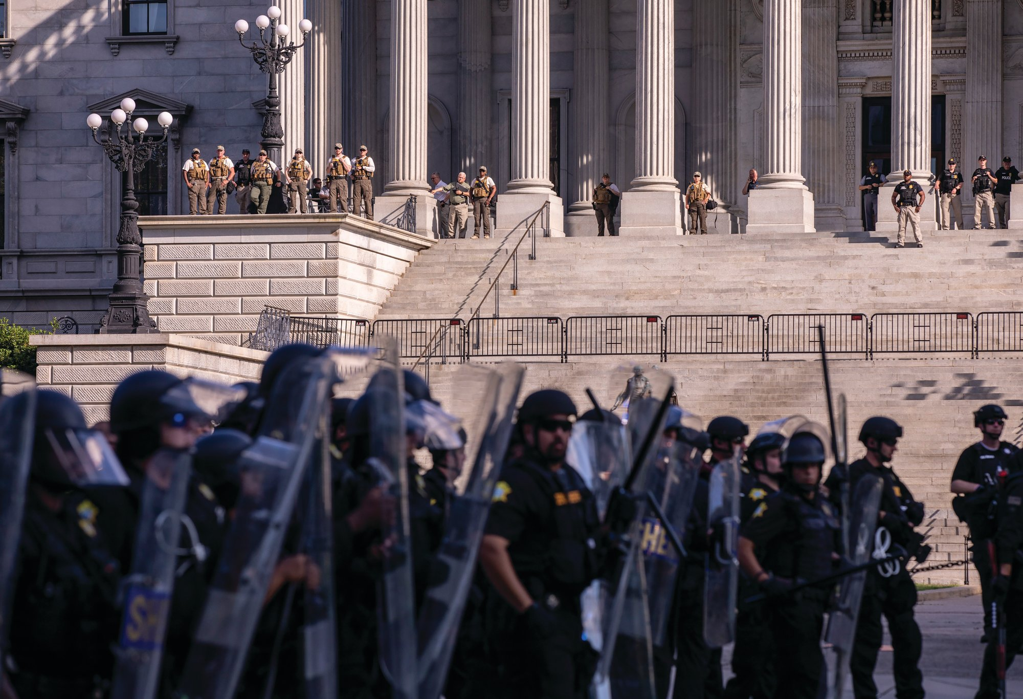 Police line up in riot gear Sunday as law enforcement officers watch from the Statehouse stairs in Columbia. Columbia Police and the Richland County Sheriff's Department enacted a curfew on Sunday night.
