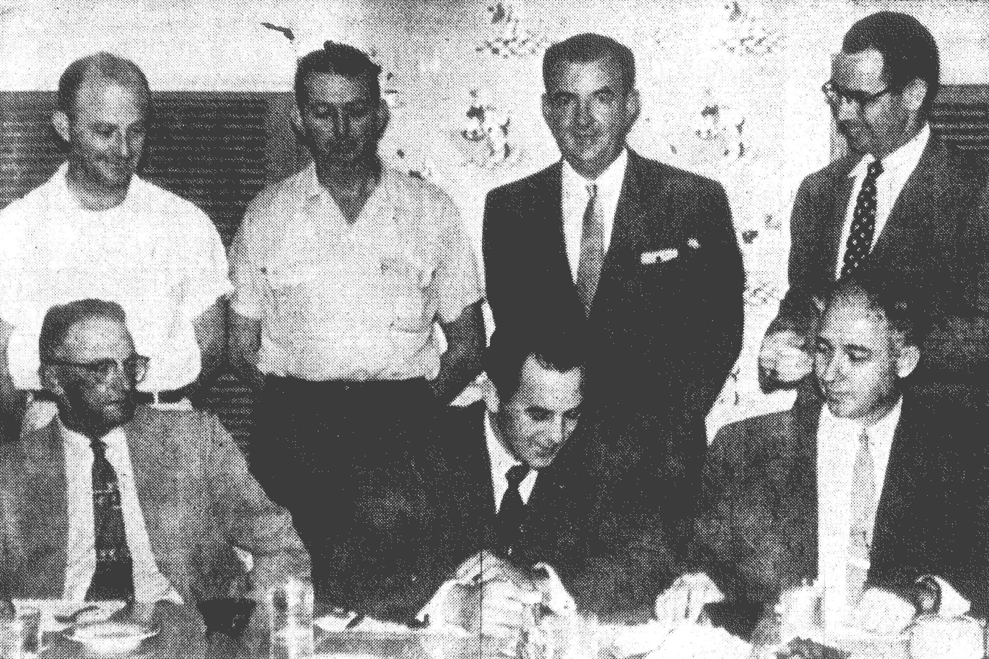 Sumter Chamber of Commerce, city and industrial officials clear up final details in negotiations Aug. 11, 1955, for the location of Model Dye Southern Inc. in Sumter. Seated from left are Mayor Pro Tem S. A. Harvin, Model Dye President Rene Petit and Chamber President C. C. Goodwin, and standing from left are W. M. Hodge, City Manager Wade S. Kolb, W. T. McCracken and Chamber Manager Worth D. Holder.