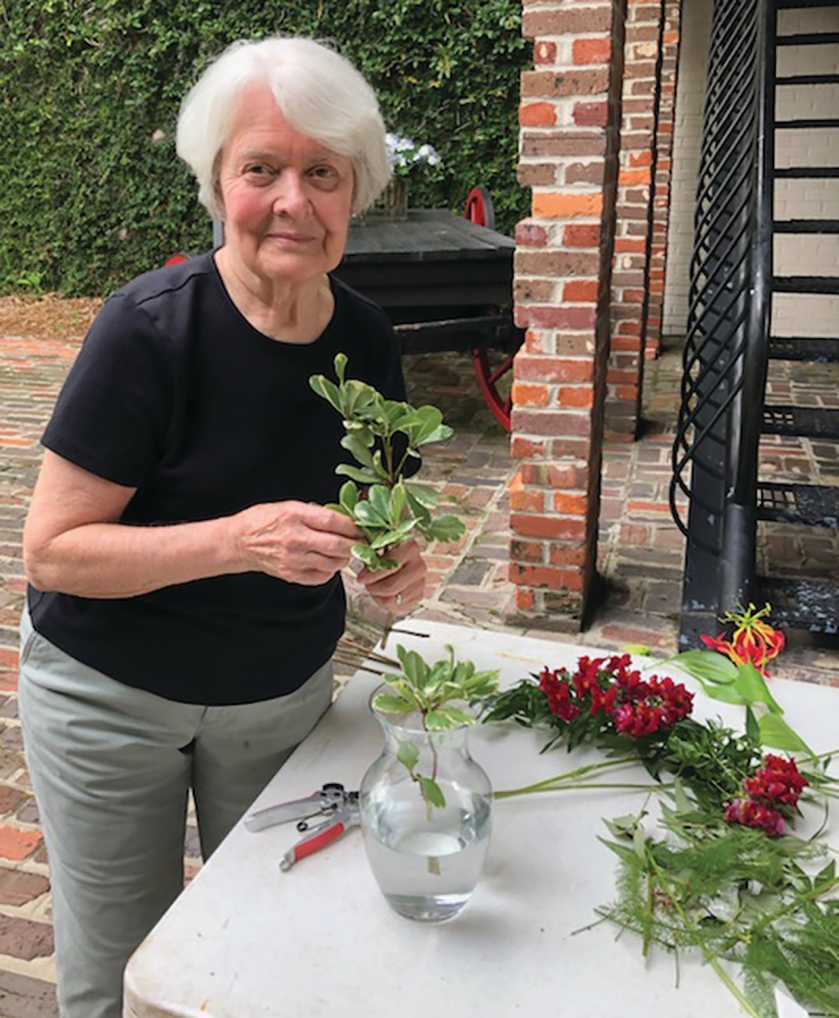 Azalea Garden Club member Mary Lou Schoeck prepares one of the flower arrangements that club members designed and delivered to Manning businesses and civic organizations as part of the club's annual community beautification project.