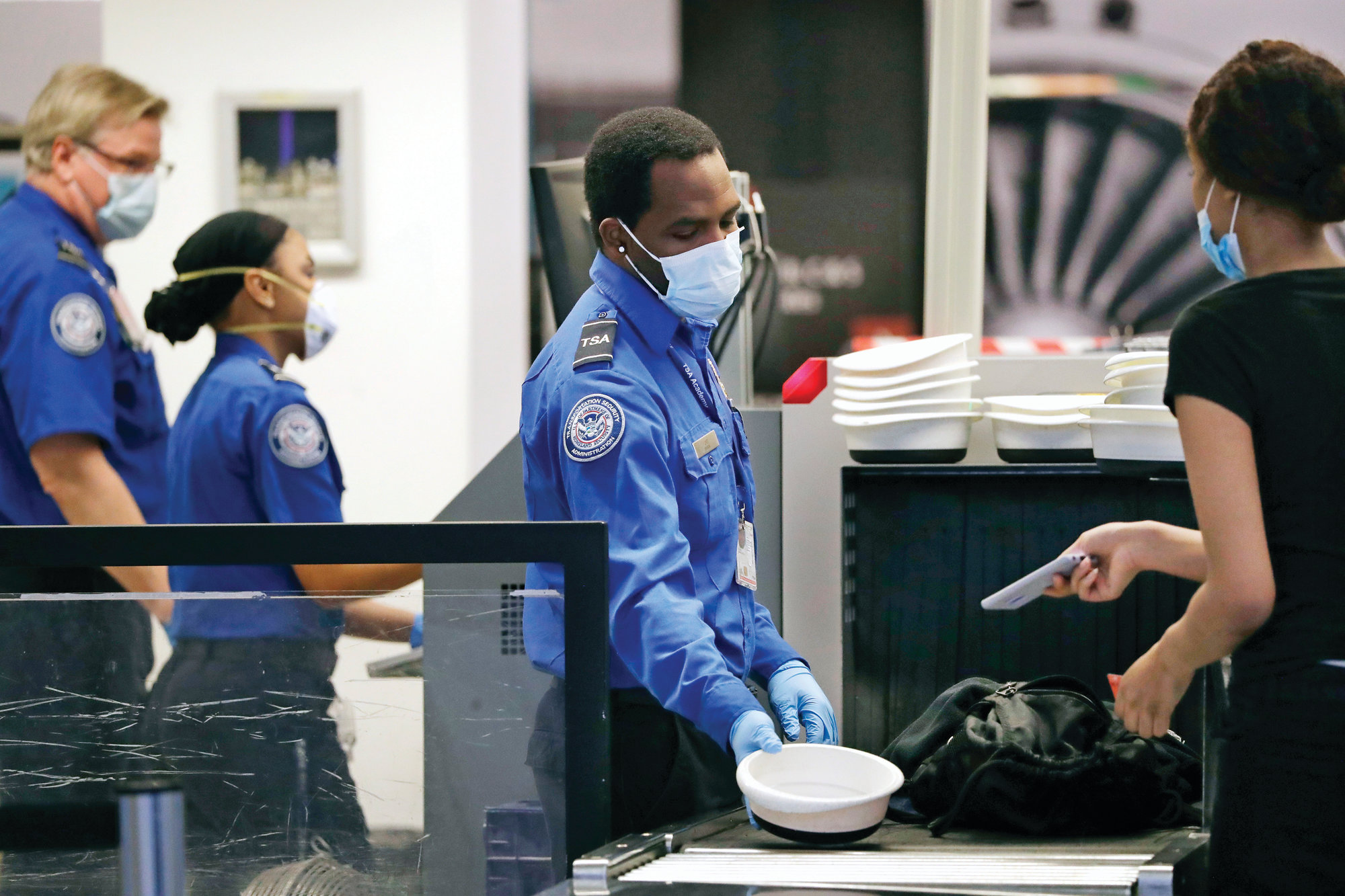 TSA officers wear protective masks at a security screening area at Seattle-Tacoma International Airport  in SeaTac, Wash. A high-ranking Transportation Security Administration official says the agency is falling short when it comes to protecting airport screeners and the public from the new coronavirus, according to published reports. A federal office that handles whistleblower complaints has ordered an investigation.