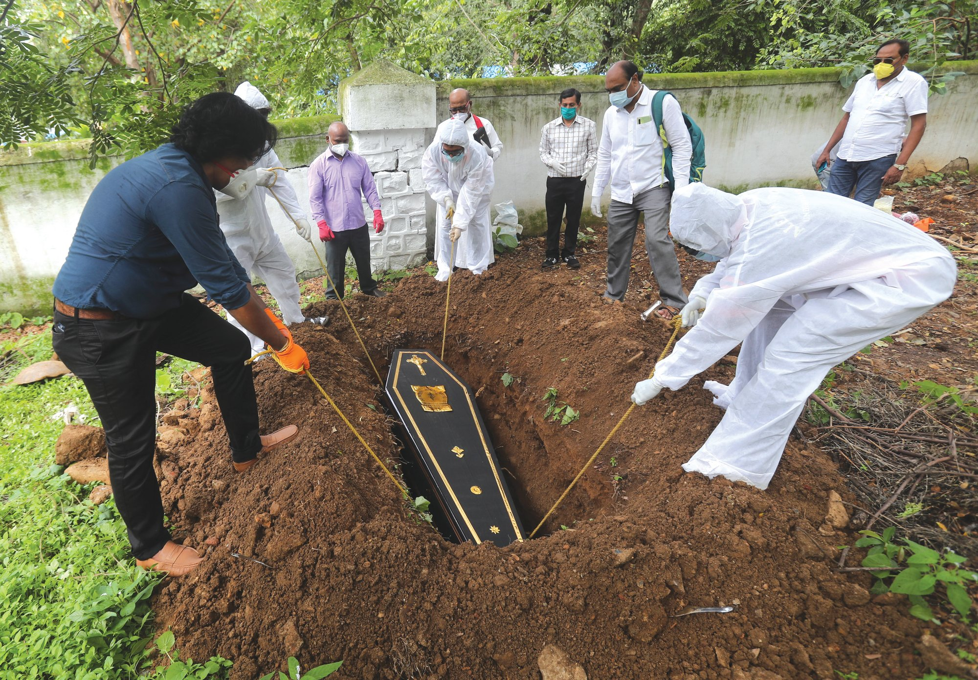 THE ASSOCIATED PRESS  People lower the coffin of a man who died of COVID-19 at a cemetery in Mumbai, India, on Tuesday. Some Indian states Tuesday were considering fresh lockdown measures to try to halt the spread of the virus in the nation of more than 1.3 billion.