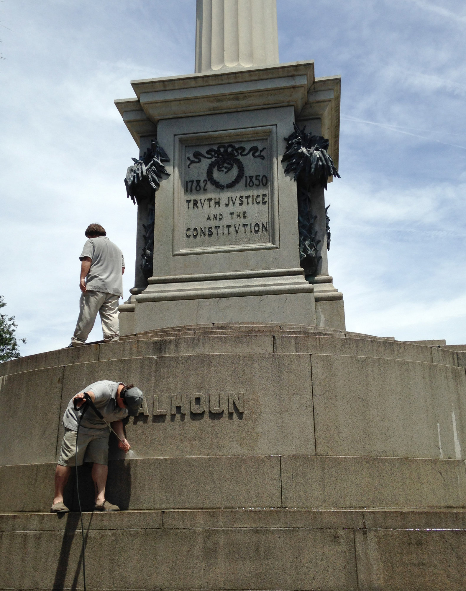 Joe Patrizzi III, a worker with Roth Restoration, power washes graffiti from a statue of John C. Calhoun in 2015 in Charleston. The statue has been removed from Marion Square.