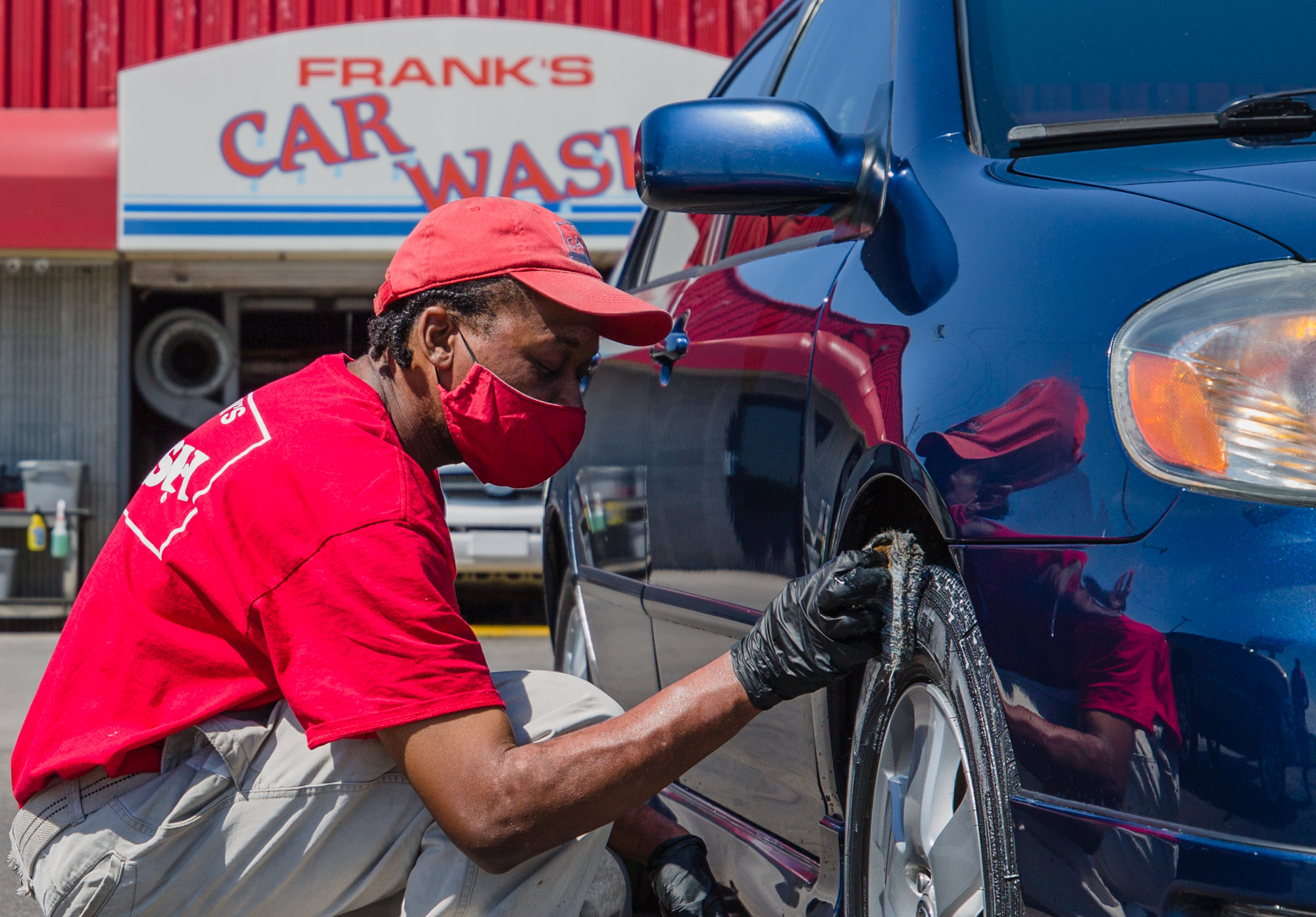As business reopen and try to maintain safety, Eric Holland shines the tires of a car at Frank's Car Wash on Broad Street in Sumter on May 6. Holland has worked at at the car wash for four years.