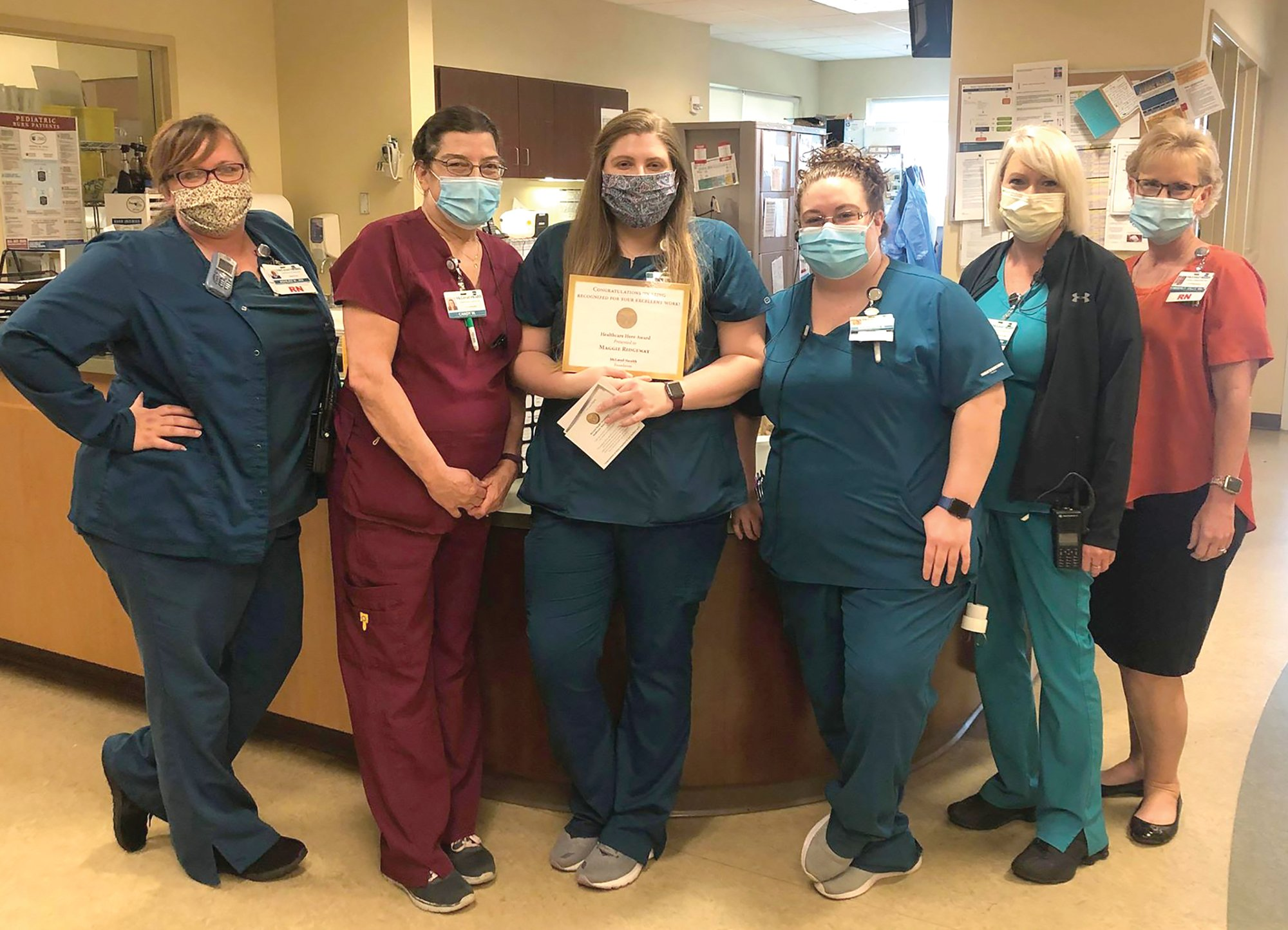 "Maggie Ridgeway, center, recently received the McLeod Heathcare Hero award. Ridgeway, who is seen with several co-workers in McLeod Health Clarendon's emergency room, is an Emergency Department Tech who was recognized for her ""compassionate care and dedication."""