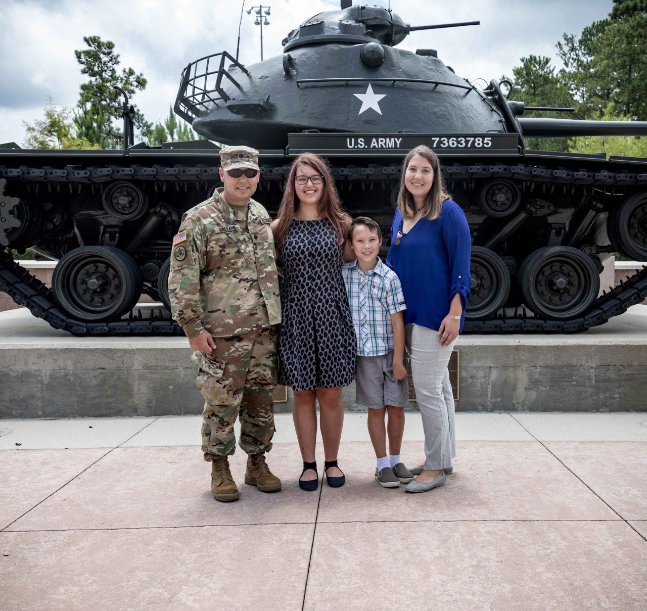On the left, U.S. Army Lt. Col. Rick Galeano, from the U.S. Army Central's Commander's Initiatives Group, stands with his family in front of the USARCENT Headquarters Building on July 1. Katrin Galeano, on the right, stands on the other side of the family, after receiving the Meritorious Public Service Medal, the third highest honor the Department of the Army can award to a private citizen. In the background is a M48 Patton Tank.