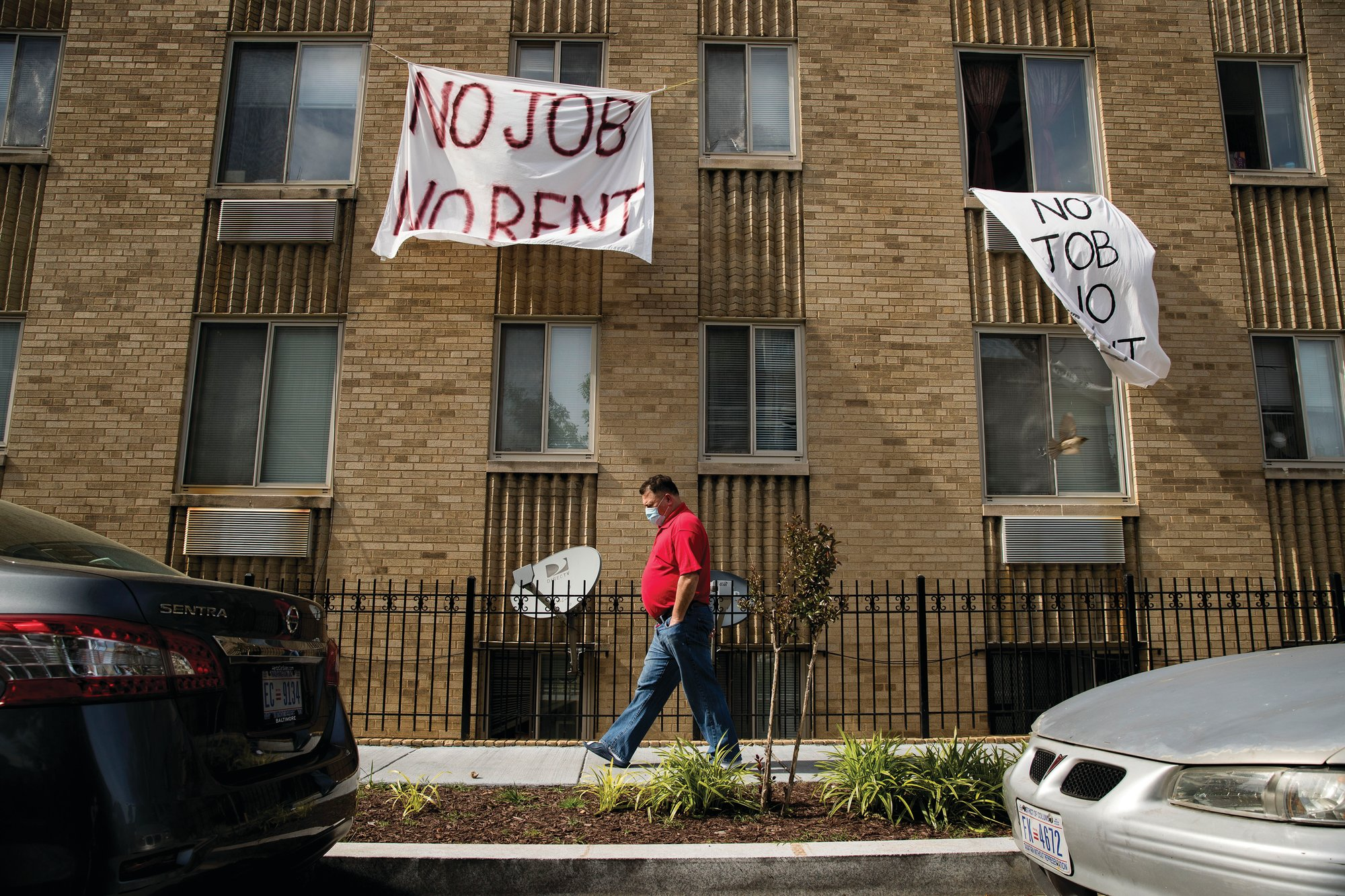 "THE ASSOCIATED PRESS  ""No Job No Rent"" signs hang from the windows of an apartment building in Northwest Washington."