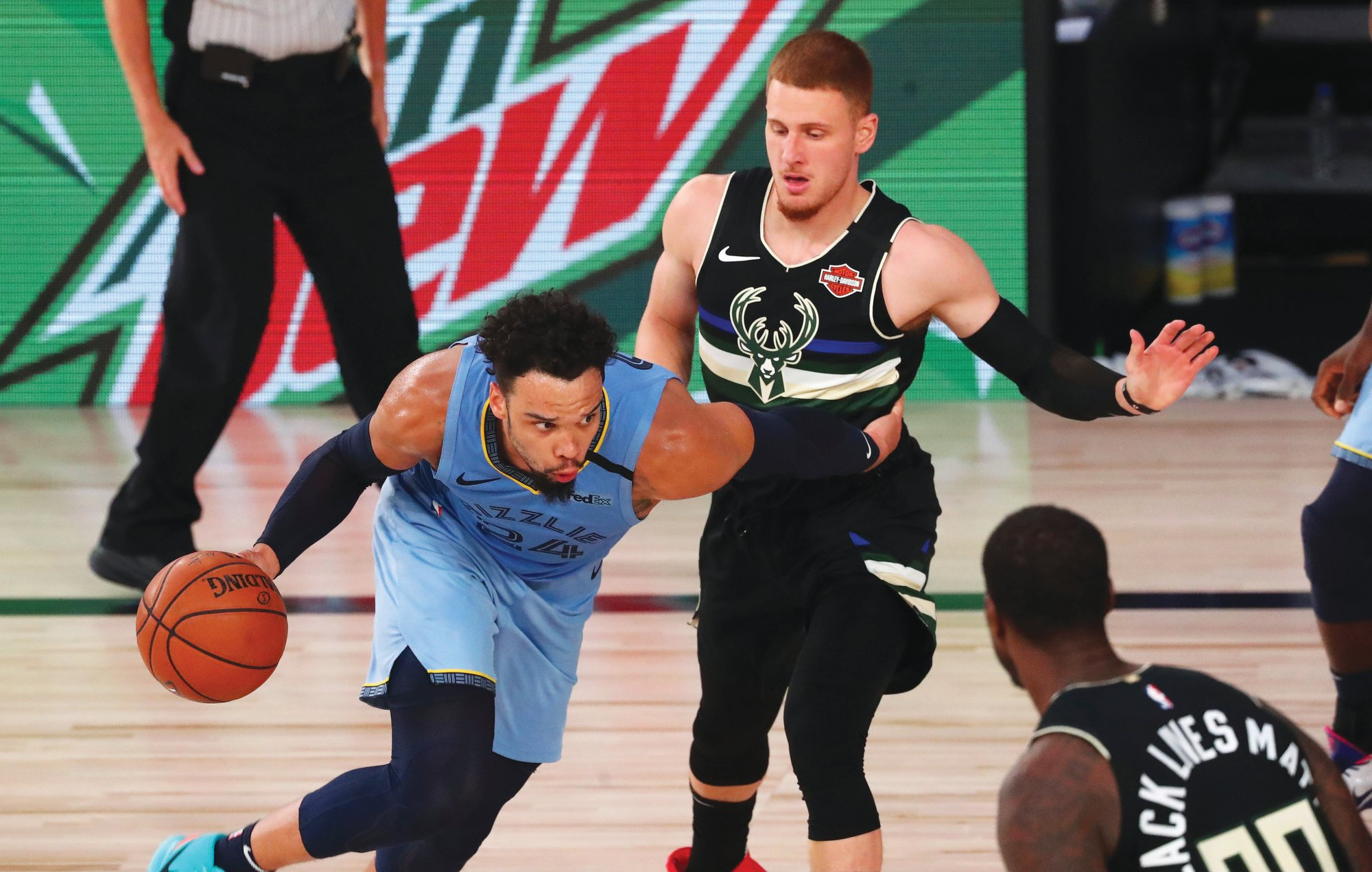 Memphis guard Dillon Brooks (24) drives against Milwaukee Bucks guard Donte DiVincenzo, top right, during the Grizzlies' 119-106 win on Thursday in Lake Buena Vista, Florida.