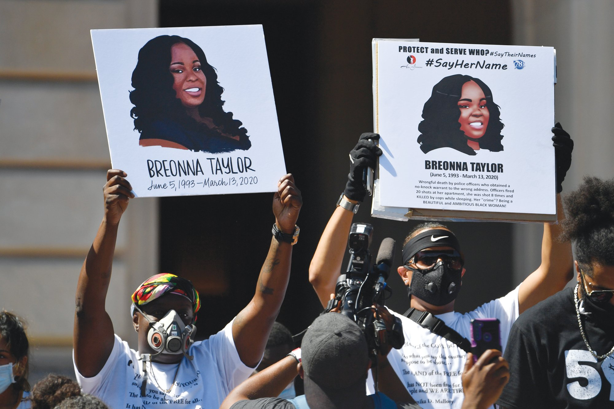 Signs showing Breonna Taylor are held during a rally in her honor on the steps of the Kentucky State Capitol in Frankfort, Kentucky, on June 25. The city of Louisville will pay several million dollars to the mother of Breonna Taylor and install police reforms as part of a settlement of a lawsuit from Taylor's family, The Associated Press has learned.