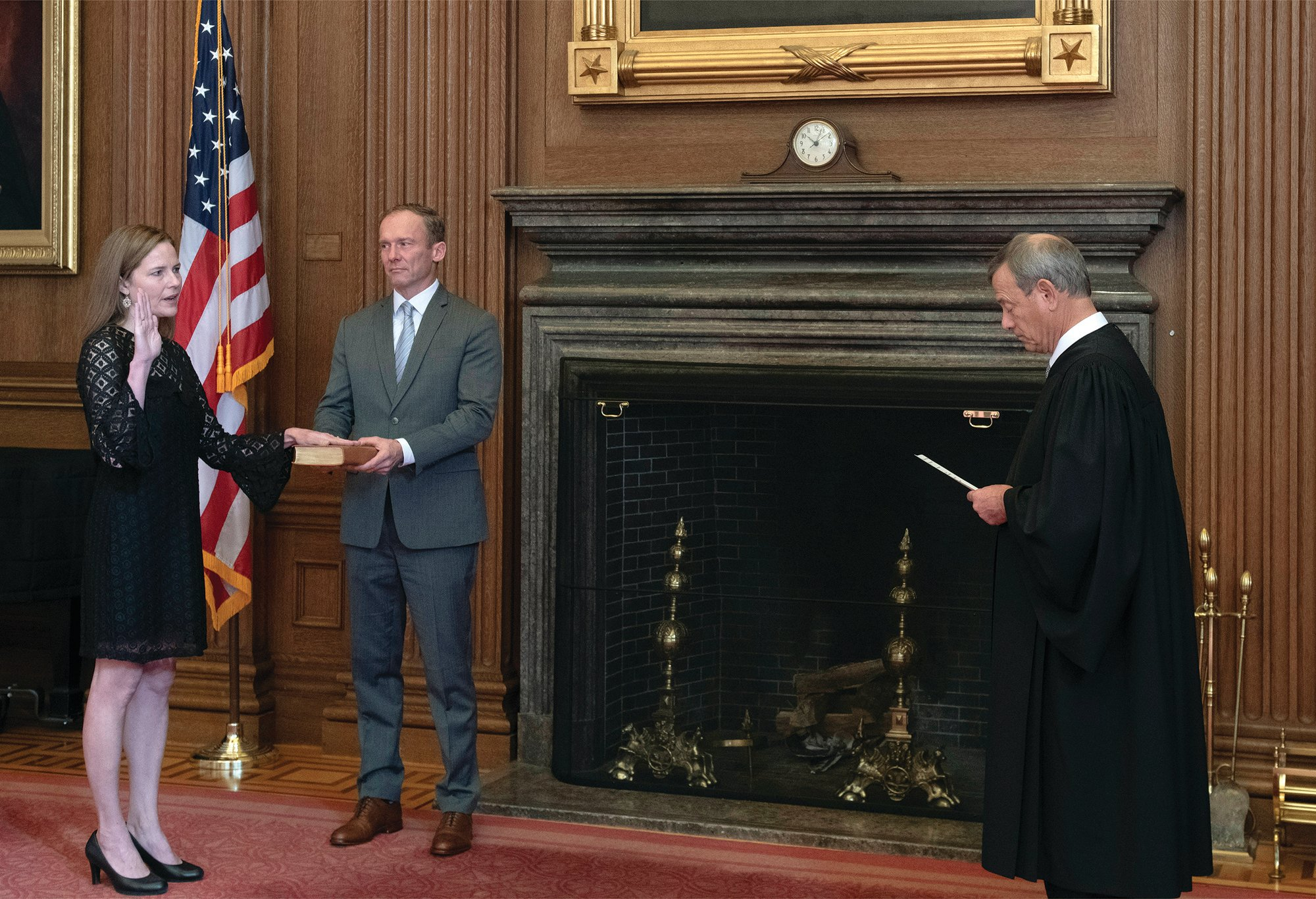 Fred Schilling / Collection of the Supreme Court of the United States via AP  Chief Justice John G. Roberts Jr., right, administers the Judicial Oath to Judge Amy Coney Barrett in the East Conference Room of the Supreme Court Building on Tuesday in Washington as Judge Barrett's husband, Jesse M. Barrett, holds the Bible.