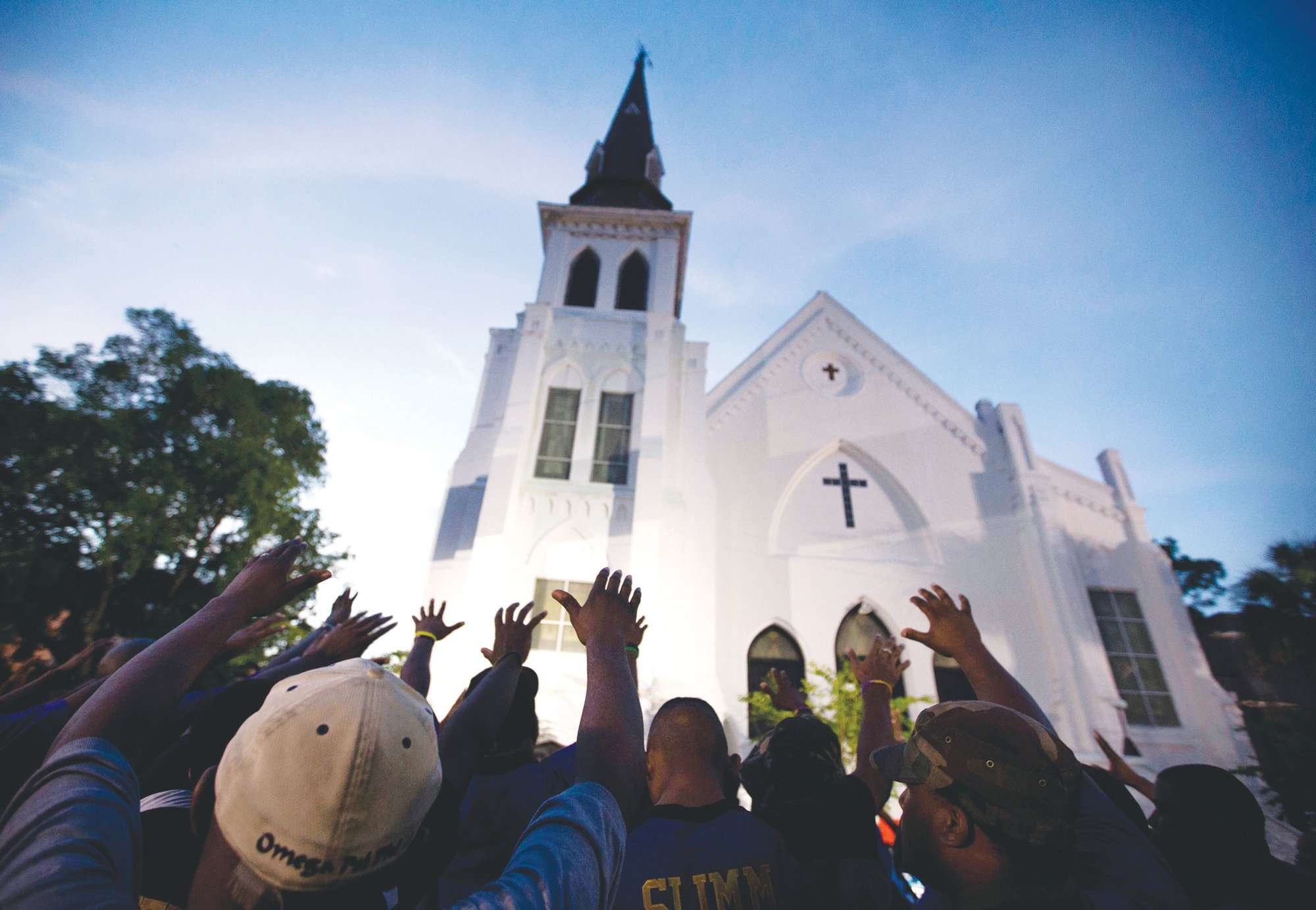 In this June 19, 2015 file photo, the men of Omega Psi Phi Fraternity Inc. lead a crowd of people in prayer outside the Emanuel AME Church, after a memorial for the nine people killed by Dylann Roof in Charleston.