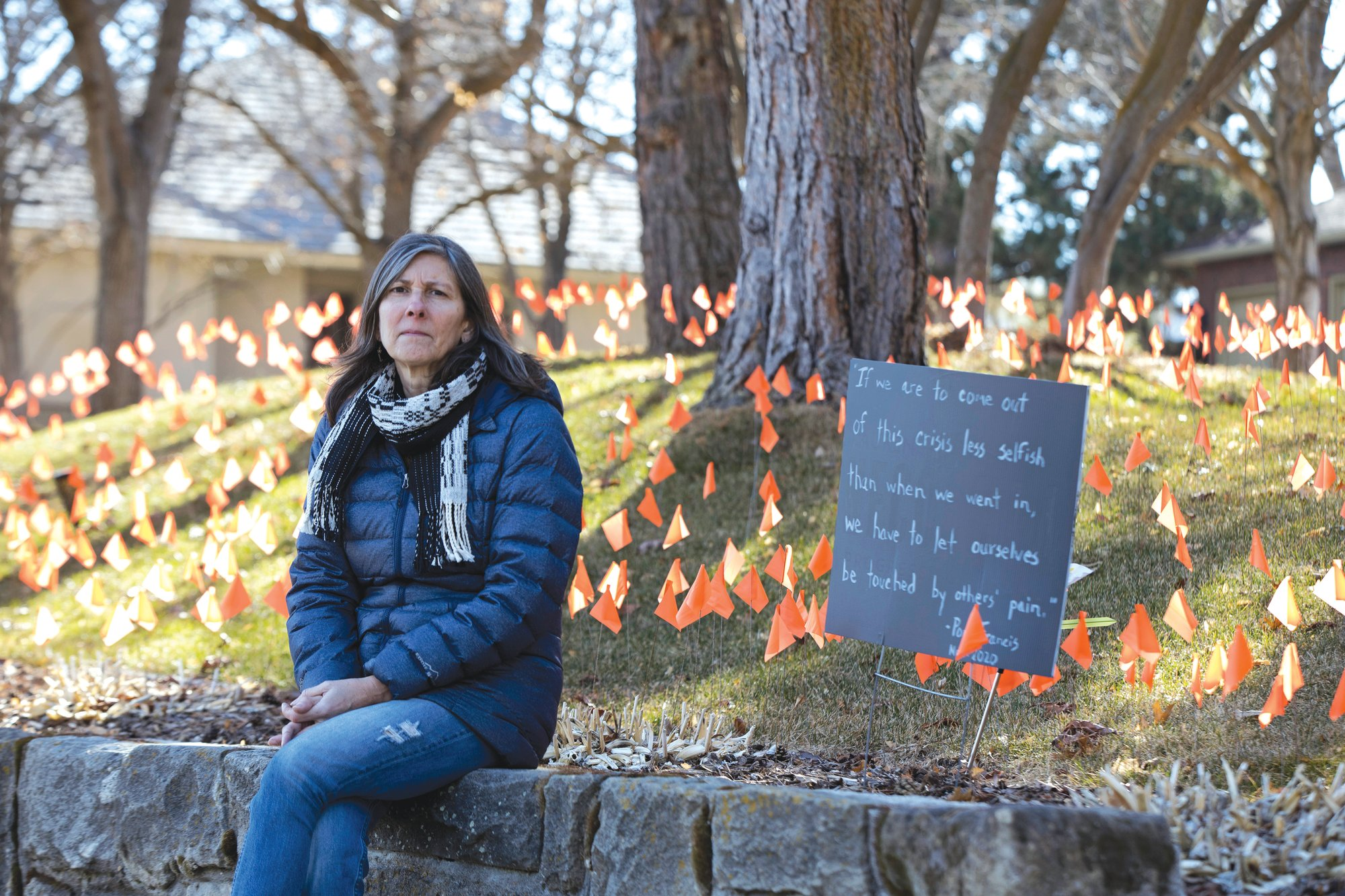 Cindy Pollock poses for a portrait in Boise, Idaho, on Feb. 10. Pollock began planting the tiny flags across her yard for each of the more than 1,800 Idahoans killed by COVID-19.