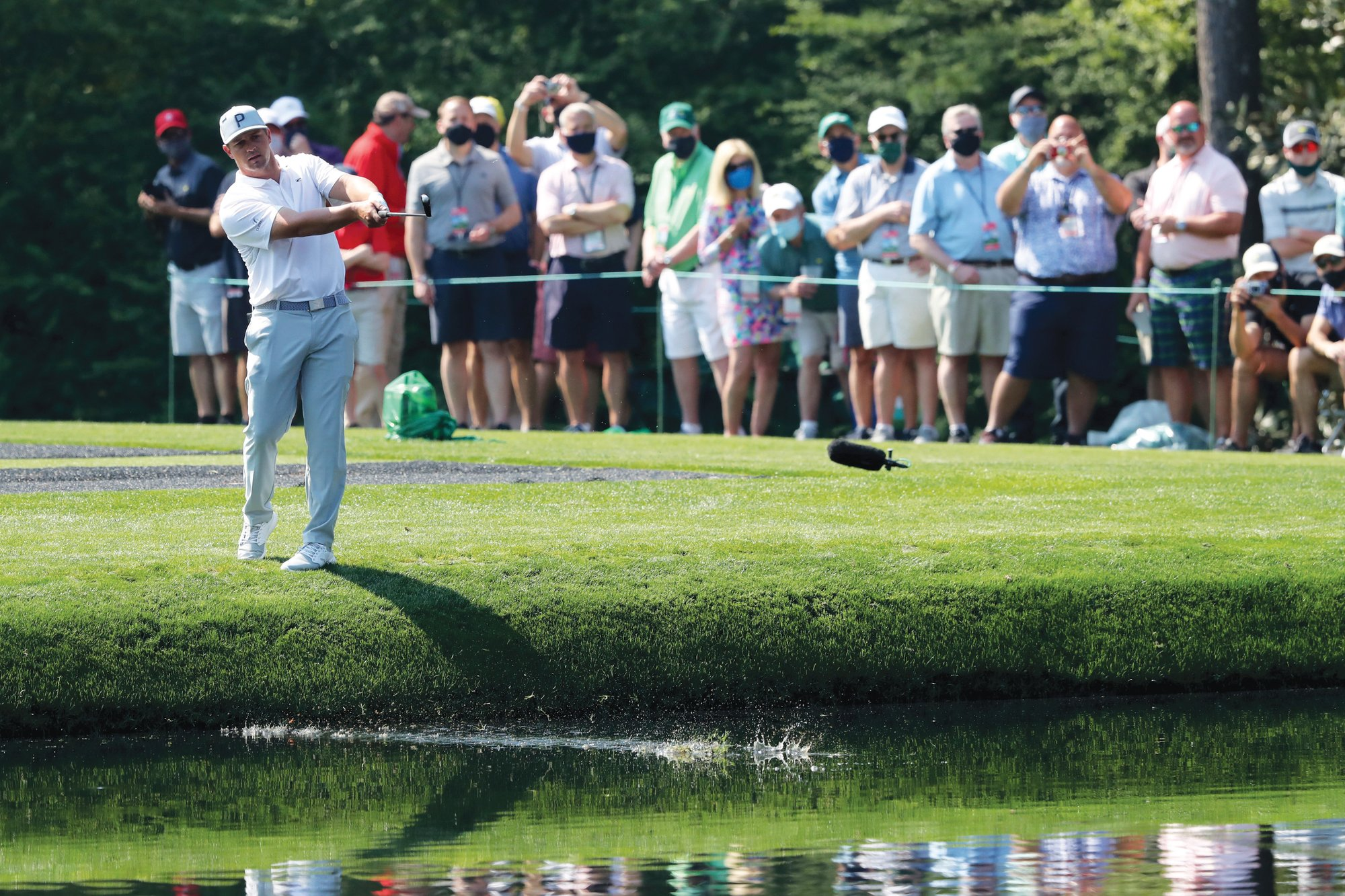 Patrons watch as Bryson DeChambeau skips his ball across the pond to the 16th green during a practice round for the Masters at Augusta National Golf Club on Wednesday.