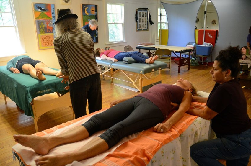 Practitioners are looking forward to meeting clients in person again, but many treatment modalities can be delivered via phone or Zoom. (Treatments at Community Health Care Day: Front to back: Jesse Scerer gives a massage, Rob Norris practices Reconnective Healing, and Mark Jordan, Energetic Chiropractic.)