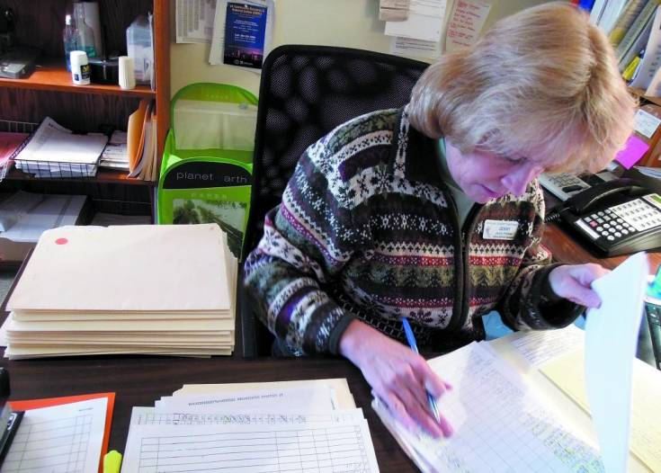Jenny Follmer, client services manager for the Douglas/Elbert Task Force, looks through the paperwork of the more than 20 families that came into the organization's Castle Rock office on Nov. 26 for assistance.