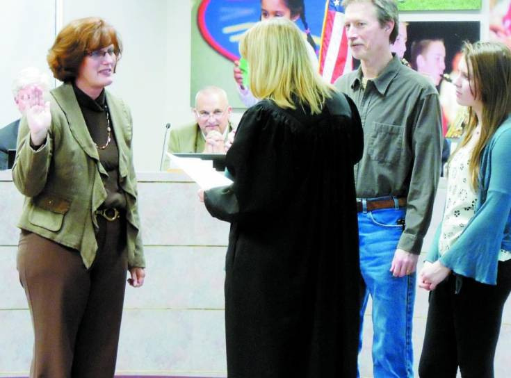 From left, incoming school board member Judi Reynolds is sworn in Dec. 5 by Judge Susanna Meissner-Cutler while board president Kevin Larsen, center, and Reyold's husband Scott and daughter Addi watch. Photo by Jane Reuter