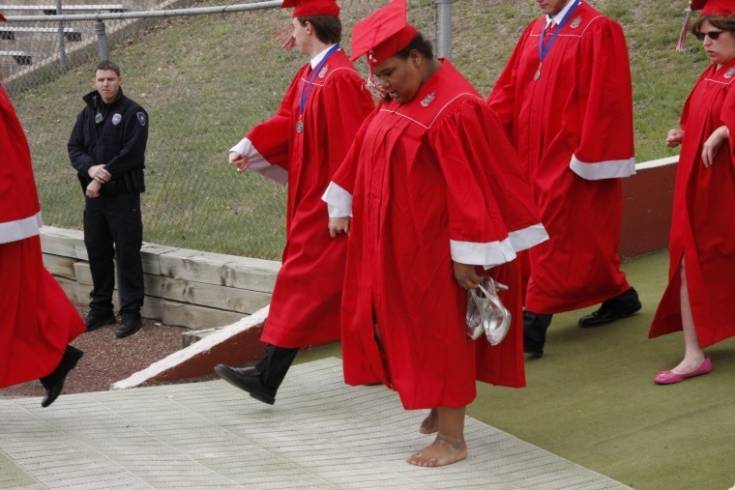 Mercedes Ramirez removed her shoes to better navigate the ramp as she and the other members of the Heritage High School Class 2011 move into Littleton Public Schools Stadium on May 18 for commencement. She and her classmates are the 38th Heritage graduating class. Photo by Tom Munds