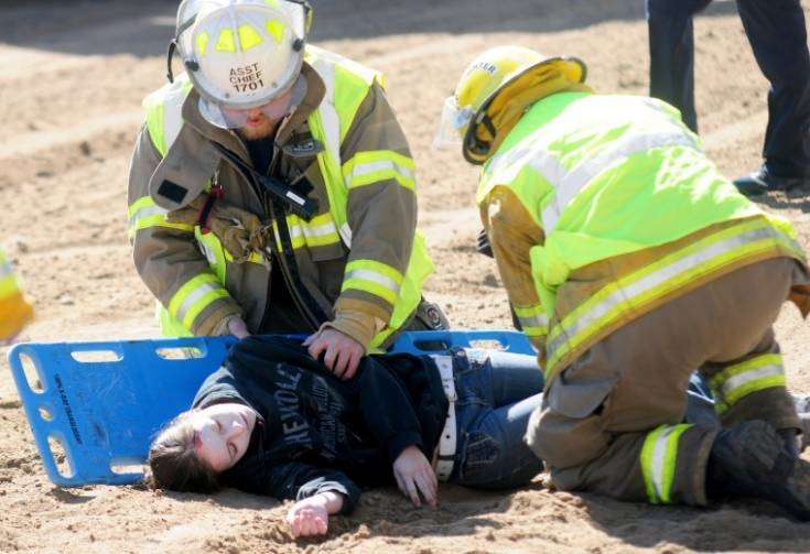 Firefighters load a fake victim onto a stretcher April 21 during a simulation at the Elbert County Fairgrounds to inform high schoolers about the dangers of drinking and driving. Photo by Courtney Kuhlen | ckuhlen@ccnewspapers.com