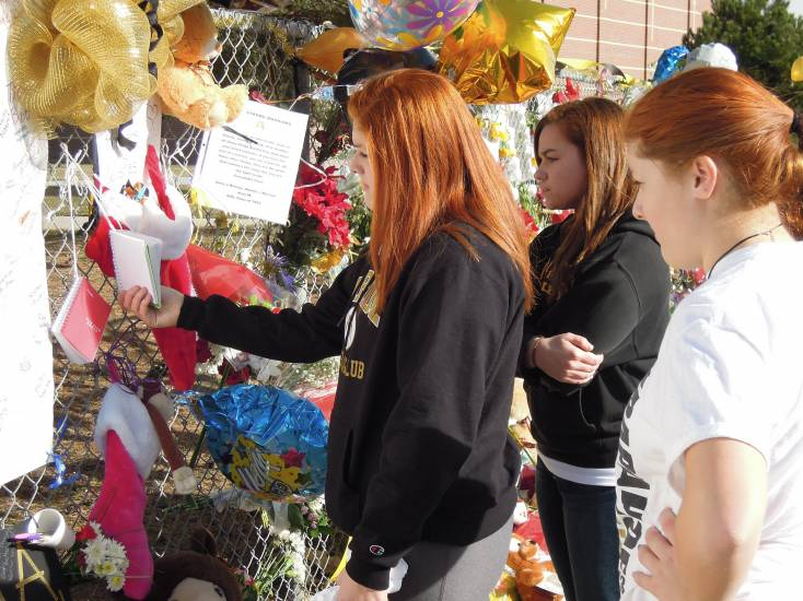"""I still don't believe it happened,"" said Arapahoe junior Tessa Serano (right, in white t-shirt) who, along with her twin sister Cheyenne (left) and fellow Arapahoe junior Caroline Powell (center), visited the memorial to Davis Thursday (Dec. 19) after picking up their personal belongings inside the high school. ""There's a lot of love here,"" said Cheyenne Serano."