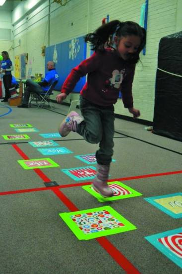 Naomi Jaquez, a first grade student, hops along the Dr. Seuss themed hopscotch as she waited, anxiously, for a book.