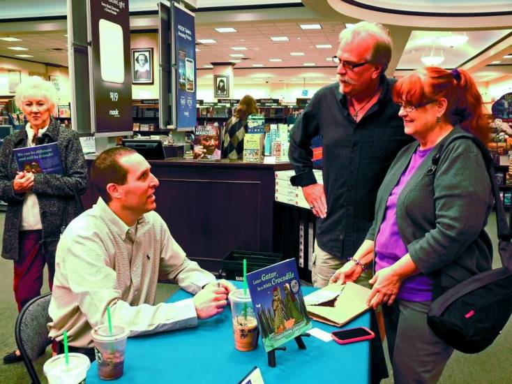 Mike Fortunato, left, discusses his book, Later Gator, In a While Crocodile with people during his book signing on Dec. 15 at Barnes & Noble in Westminster.