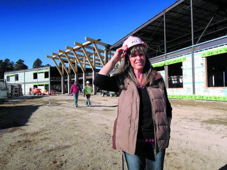 Elbert School District business manager Bev McGuire dons a hard hat Dec. 17 at the construction site of the new $20.6 million Elbert school. McGuire said the project remains on track to open in the fall of 2014.
