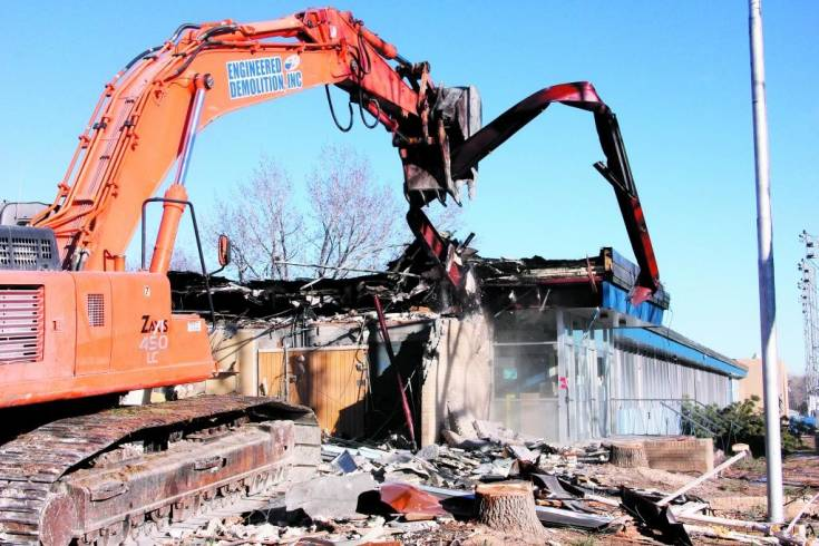 The excavator operator pulls to remove one of the steel support beams as demolition begins Dec. 23 on the main Englewood HIgh School buildings. Demolition will take four to five weeks and, once the area is cleared, work will begin on Phase Two construction of a seventh- through-12th-grade campus on the site.